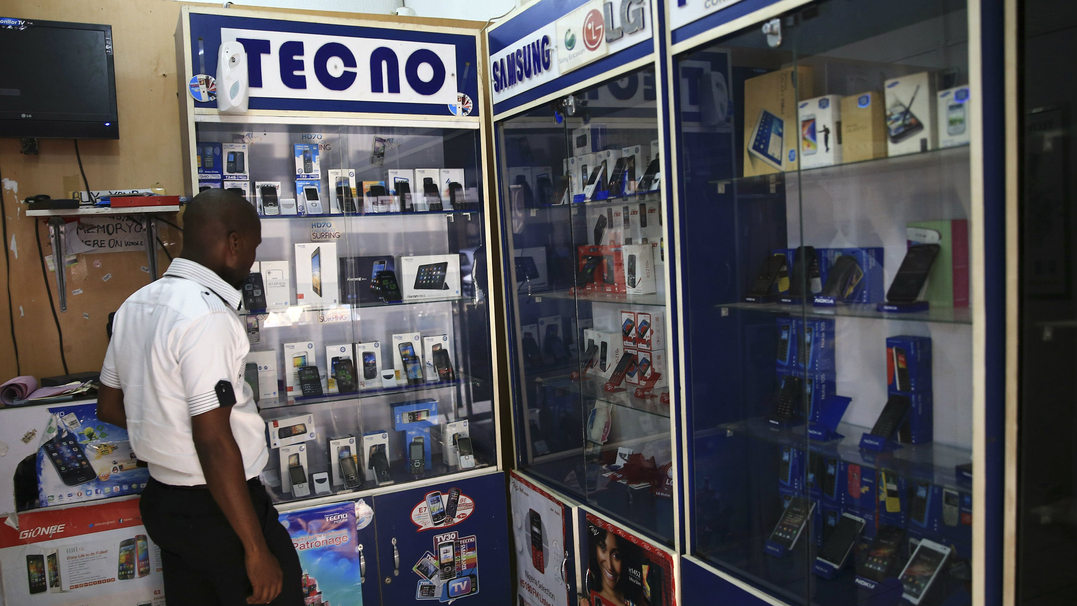 A man looks at smartphones on display at a shop at Wuse II business district in Abuja December 9, 2014. Nigeria is suffering from a plummeting currency, steep budget cuts, corruption scandals and diving oil prices; yet all this is unlikely to decide a tight race for the presidency. When the central bank devalued the naira last month to save foreign reserves, the impact was felt instantly on the streets. Nigeria imports 80 percent of what it consumes. Picture taken December 9, 2014. REUTERS/Afolabi Sotunde (NIGERIA - Tags: BUSINESS POLITICS)