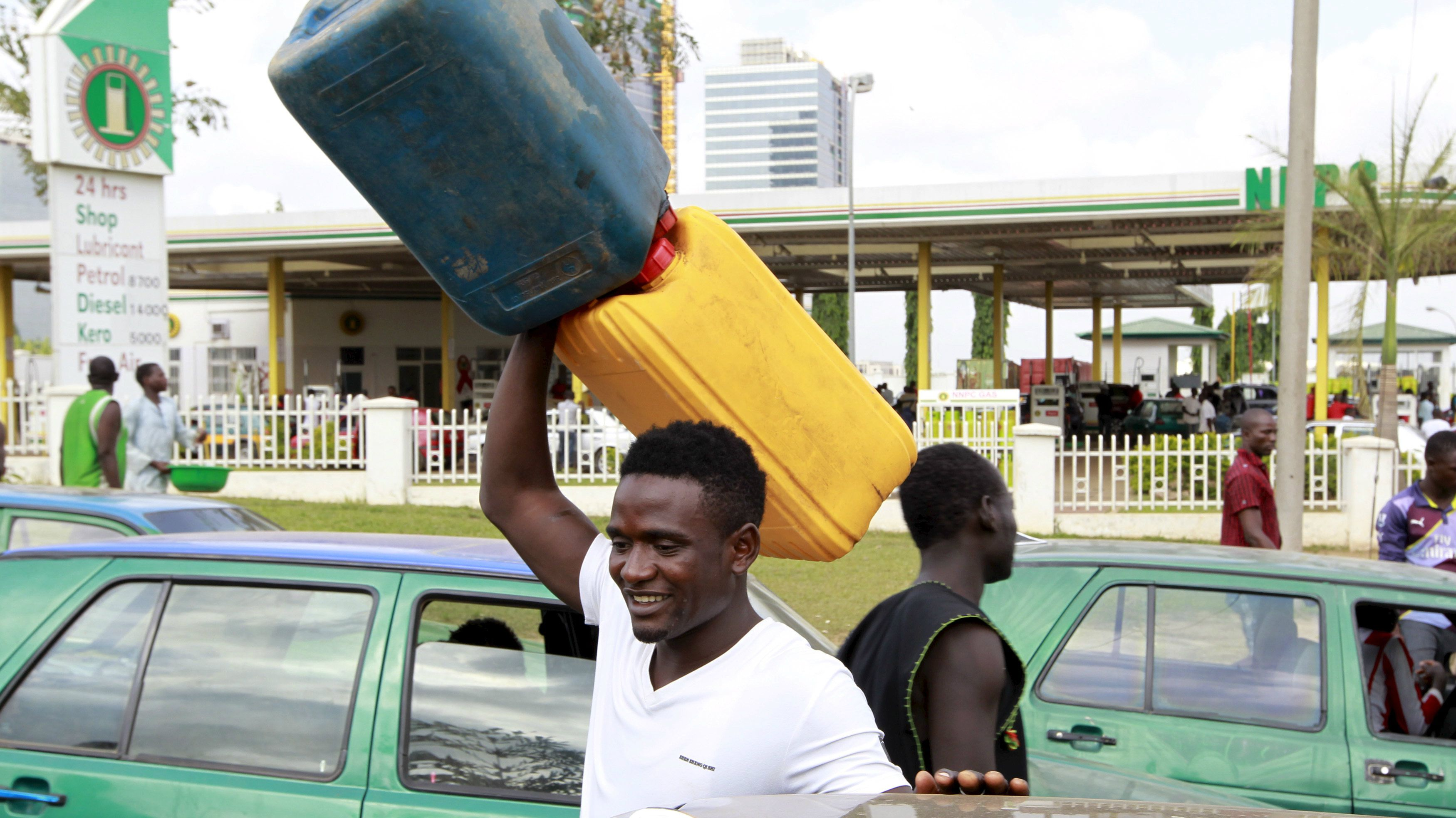 A man carries empty petrol containers outside the NNPC mega petrol station in Abuja, Nigeria May 25, 2015. REUTERS/Afolabi Sotunde