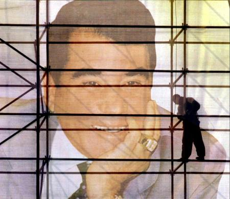 Turkmen workers work on a giant poster with a portrait of President Saparmurat Niyazov in Ashgabat, December 28, 2002.