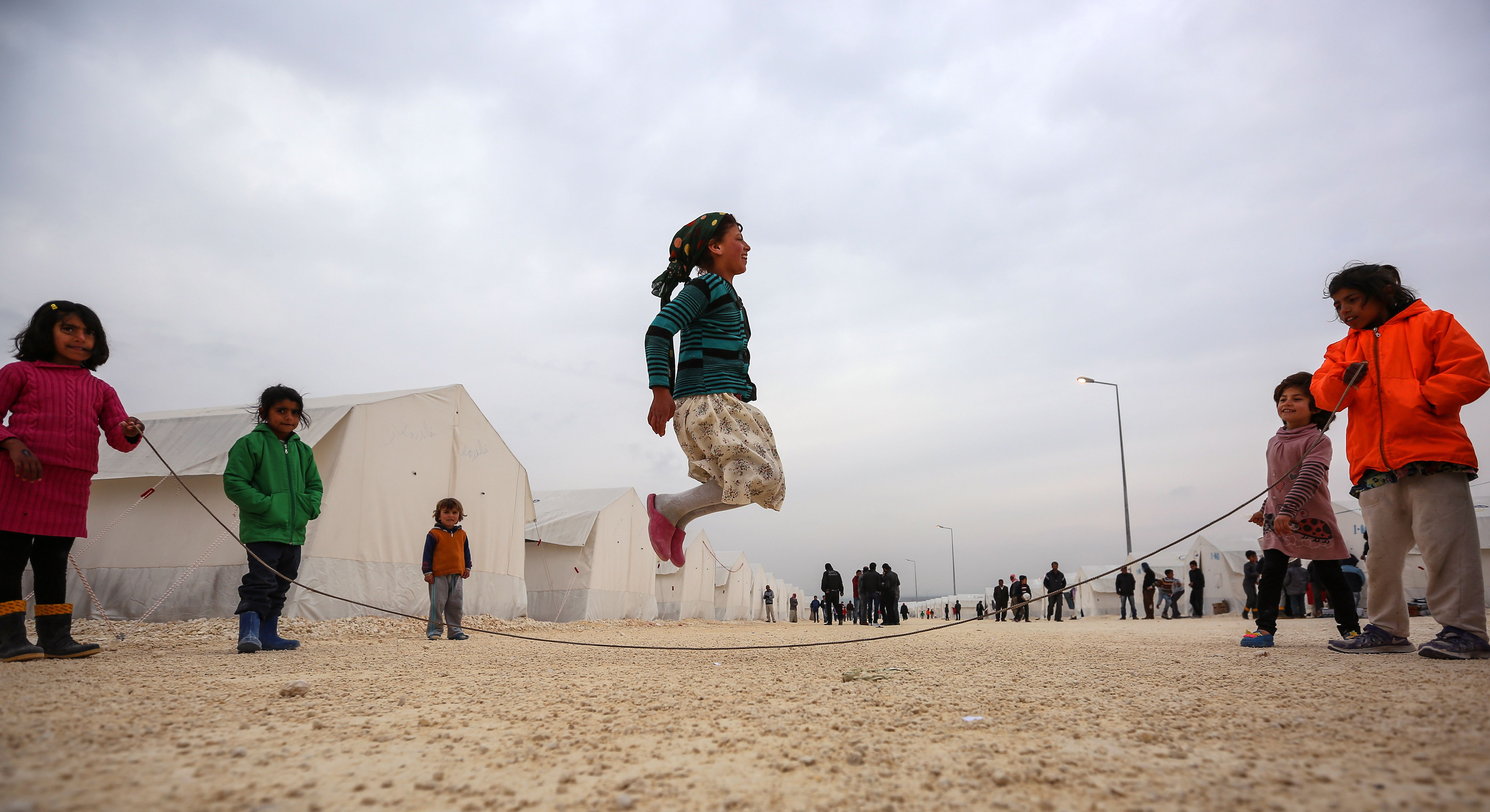 Syrian refugee children who fled violence in Syrian city of Ayn al-Arab or Kobani play their tents in Turkey's newly set-up camp in the border town of Suruc, Turkey, Friday, Jan. 30, 2015. The 35,000 people capacity camp is the biggest refugee camp in Turkey. About 200,000 people arrived in Turkey since the start of fighting between Kurdish militia and Islamic State militants mid-September, 2014. (AP Photo/Emrah Gurel)