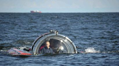 """Russia's President Vladimir Putin (L) is seen through the glass of C-Explorer 5 submersible after a dive to see the remains of the naval frigate """"Oleg"""", which sank in the 19th century, in the Gulf of Finland in the Baltic Sea July 15, 2013."""