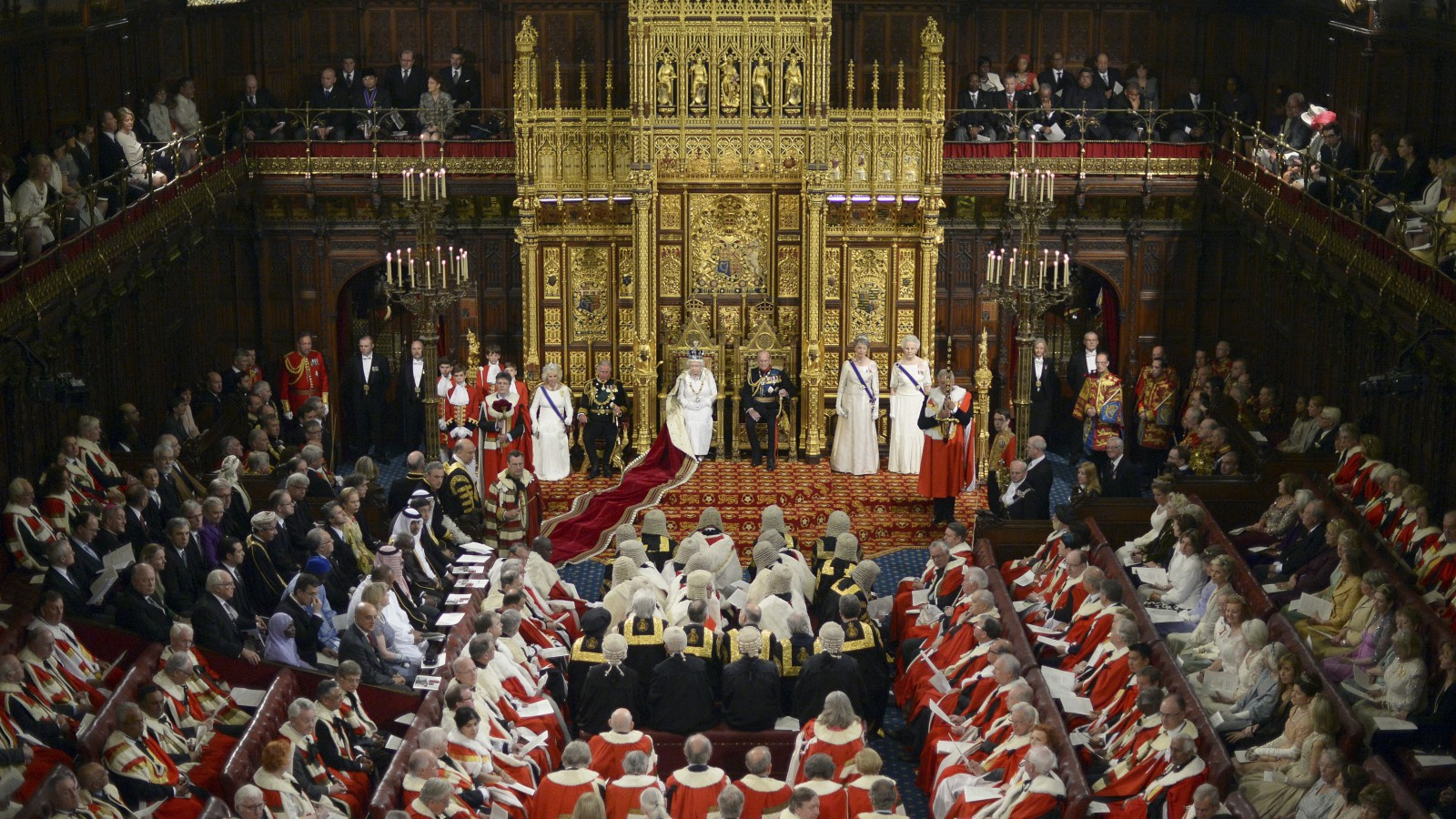 Britain's Queen Elizabeth, centre, prepares to deliver her speech in the House of Lords, during the State Opening of Parliament at the Palace of Westminster in London Wednesday June 4, 2014.  The State Opening of Parliament is an annual pageant of pomp and politics centered on the Queen's Speech, a legislative program written by the government but read out by the monarch before a crowd of lawmakers. Queen Elizabeth sits with her husband Prince Philip, and Prince Charles with Camilla Duchess of Cornwall, centre left. (AP Photo/Carl Court, Pool)