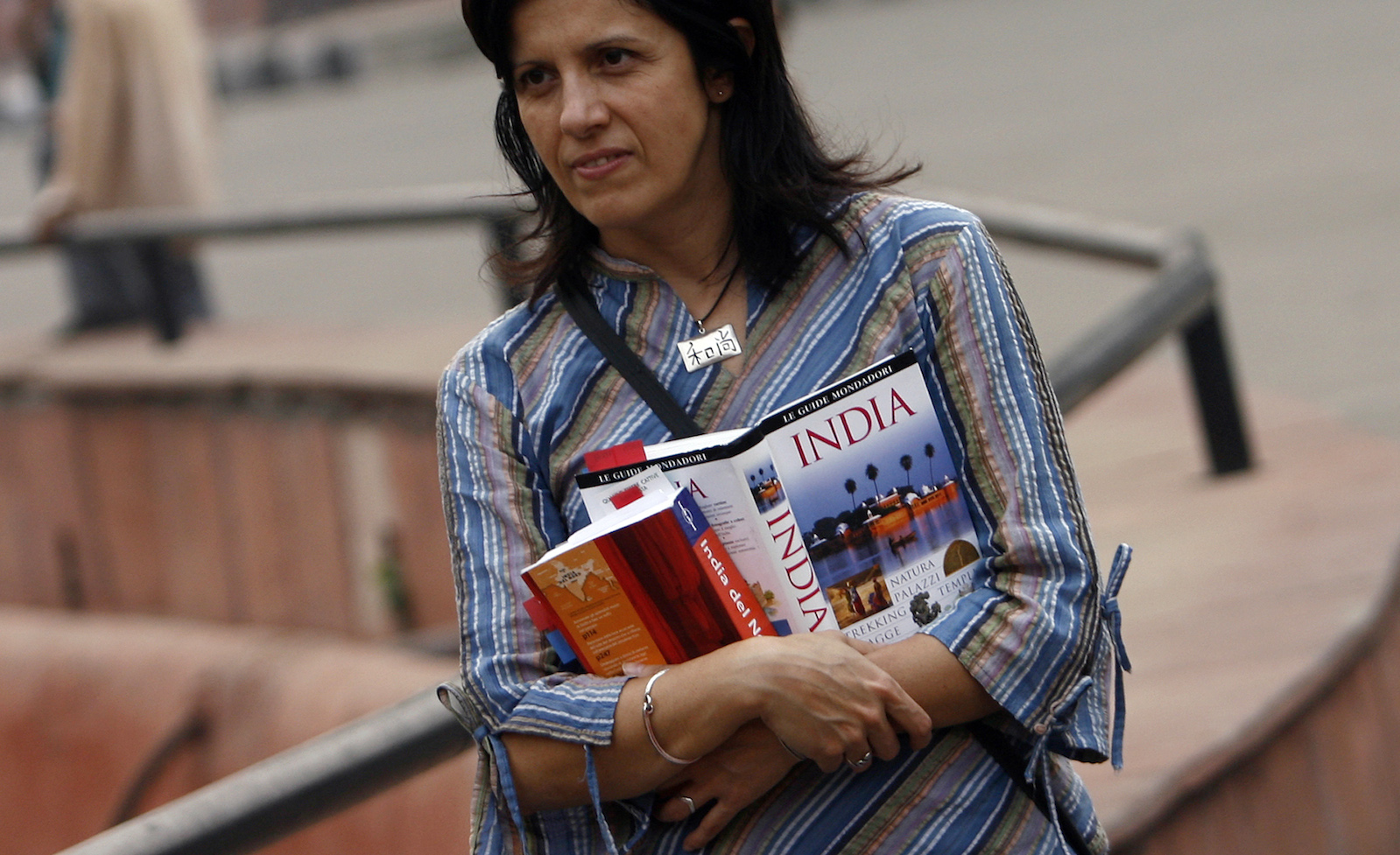A foriegn tourist holds tourist guide books as she visits the Red Fort in the old quarters of Delhi.