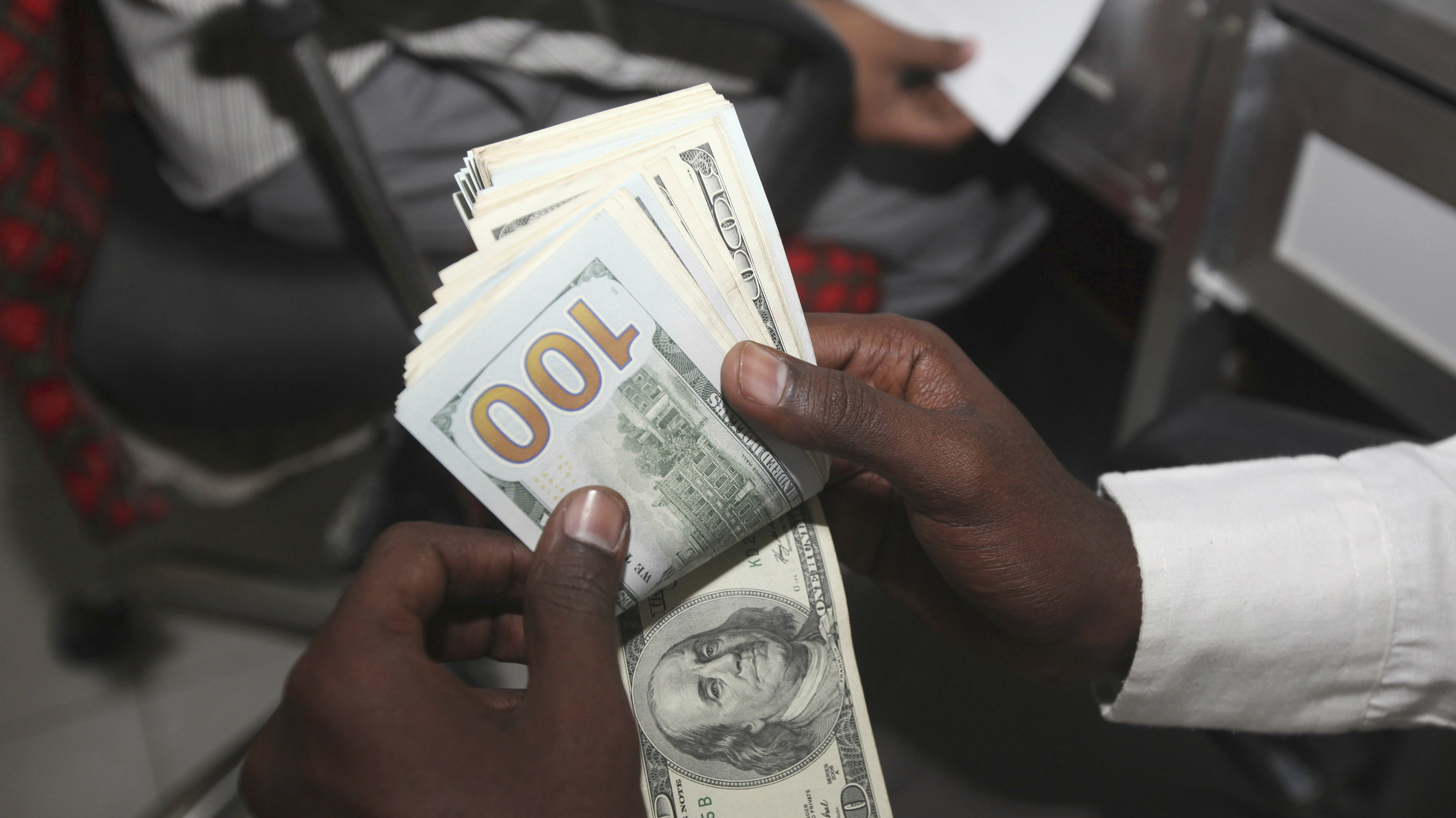 A teller counts U.S. notes at a transfer office in Mogadishu