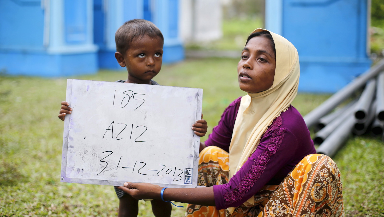 A Rohingya migrant mother (R) and her child, who recently arrived in Indonesia by boat, hold a placard while posing for photographs for immigration identification purposes inside a temporary compound for refugees in Aceh Timur regency