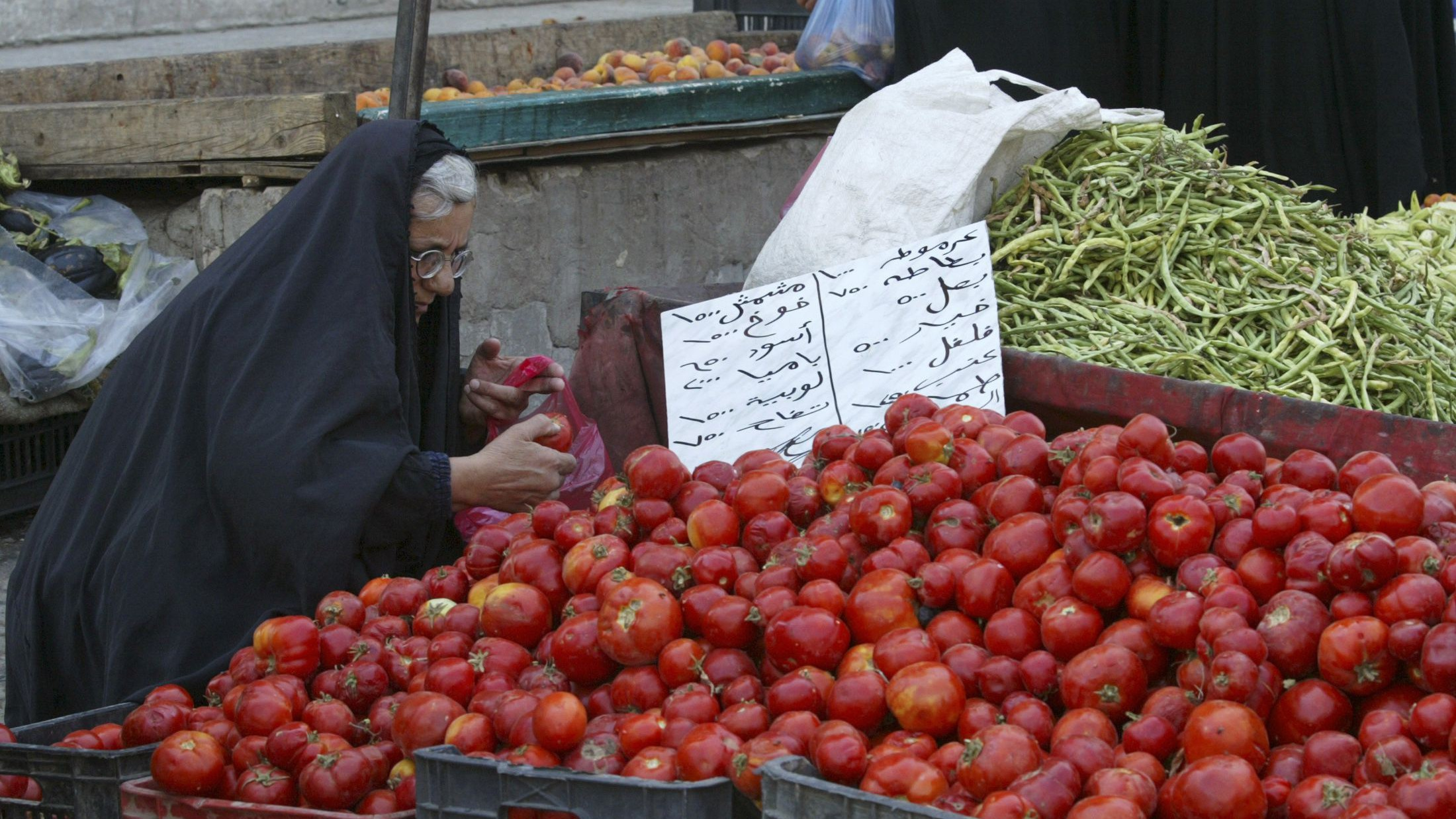 A woman buys vegetables in a market in Baghdad's Karrada district