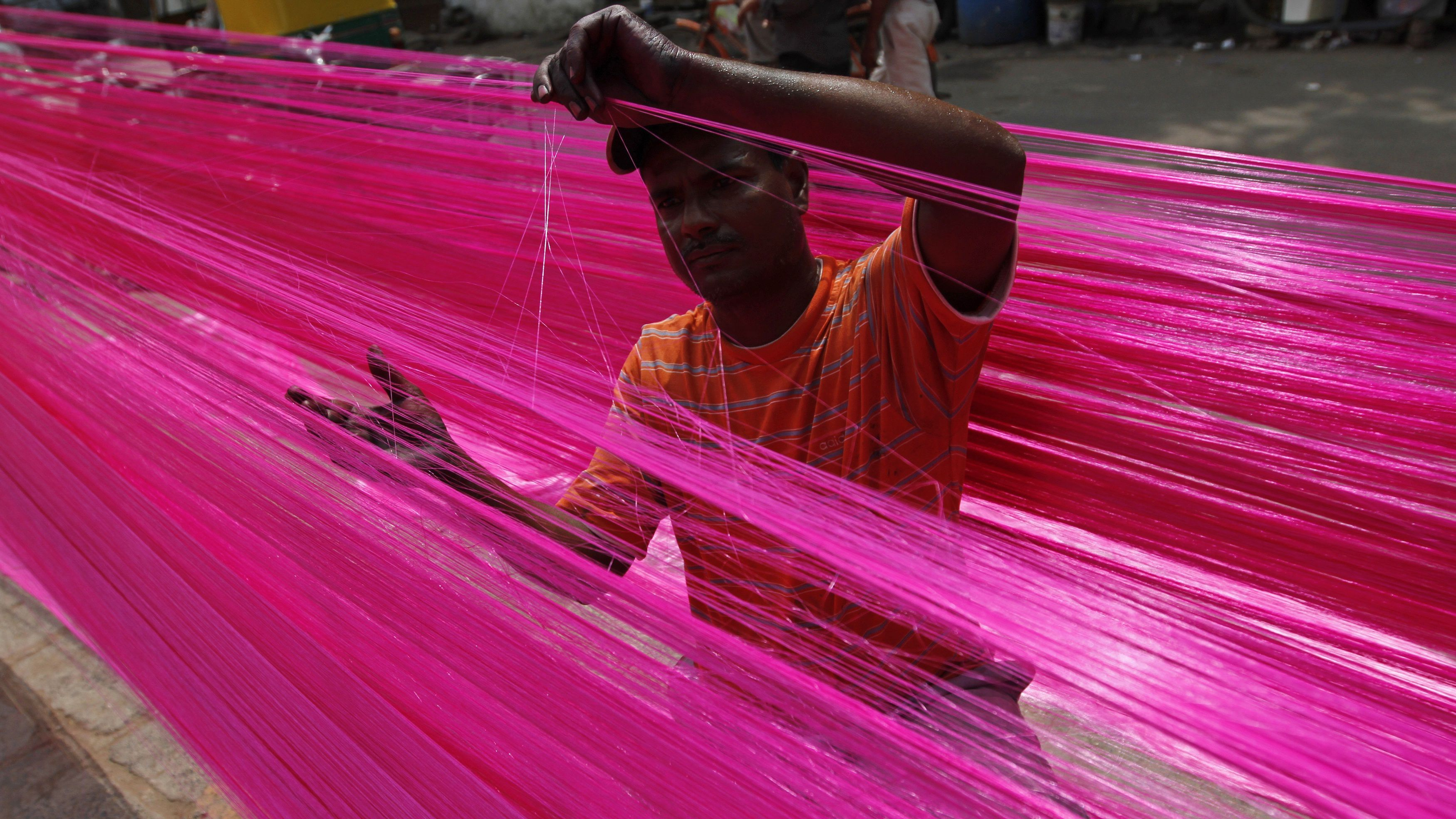 A man checks polyester thread kept for drying to make artificial garlands ahead of the Diwali festival in the western Indian city of Ahmedabad October 11, 2011. Artificial garlands are sold in large numbers during Diwali, the annual Hindu festival of lights, when people buy these to decorate their homes.