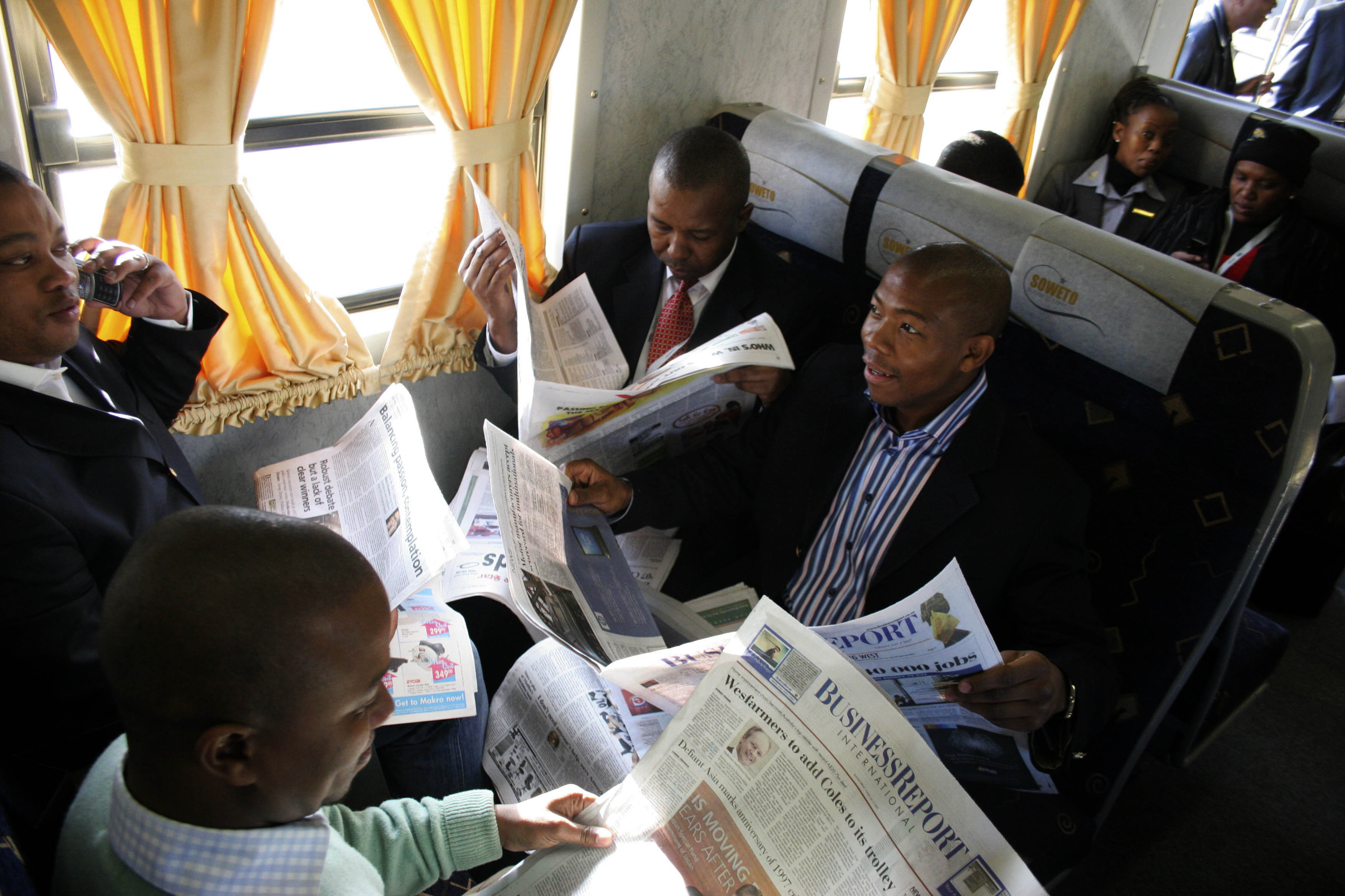 Passengers read newspapers on a business express train in Johannesburg.