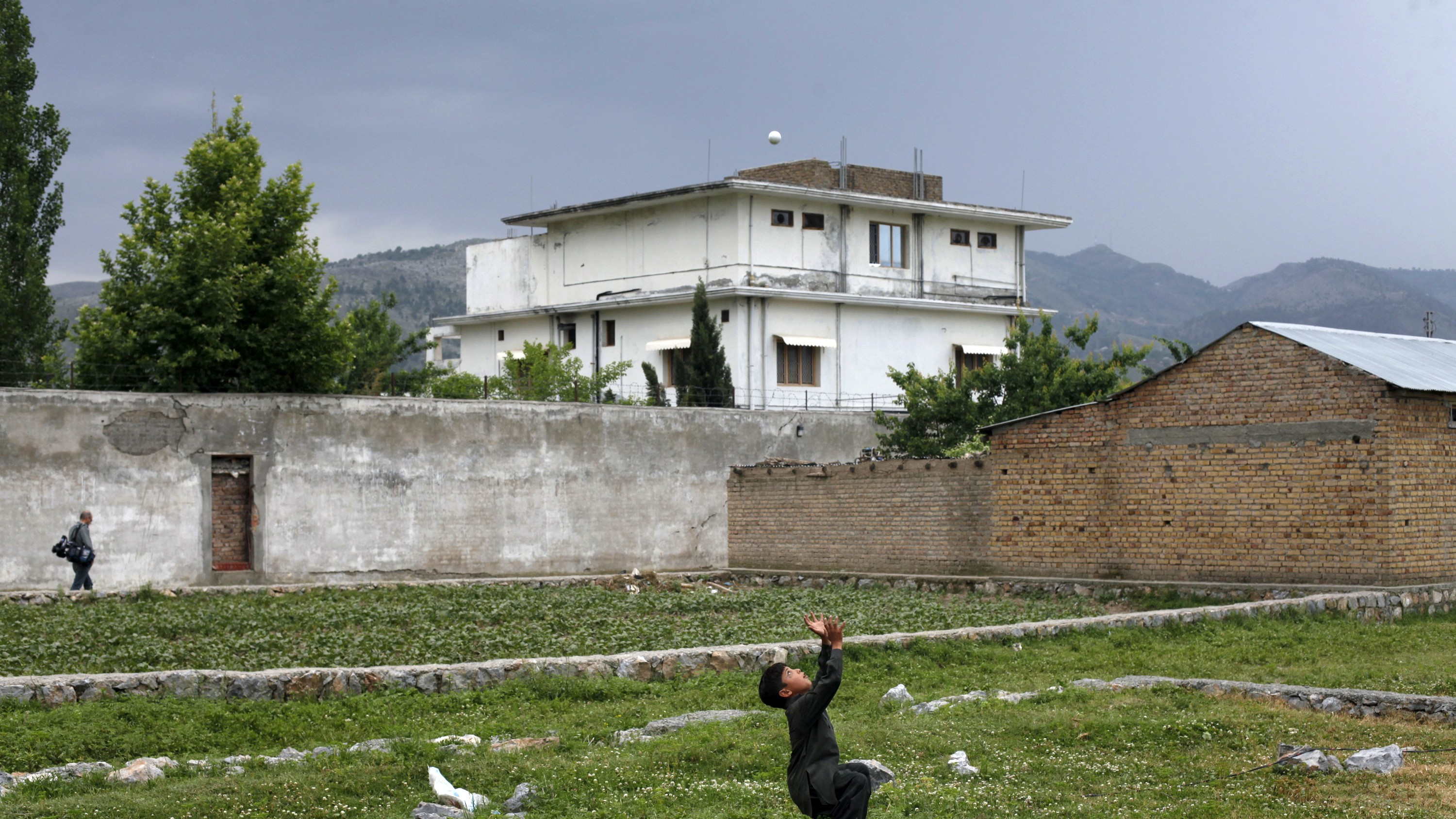 A boy plays with a tennis ball in front of Osama bin Laden's compound in Abbottabad in this May 5, 2011 file picture. Osama bin Laden was killed almost a year ago, on May 2, 2011, by a United States special operations military unit in a raid on his compound in Abbottabad.