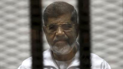 Ousted Egyptian President Mohamed Morsi is seen behind bars during his trial at a court in Cairo May 8, 2014.