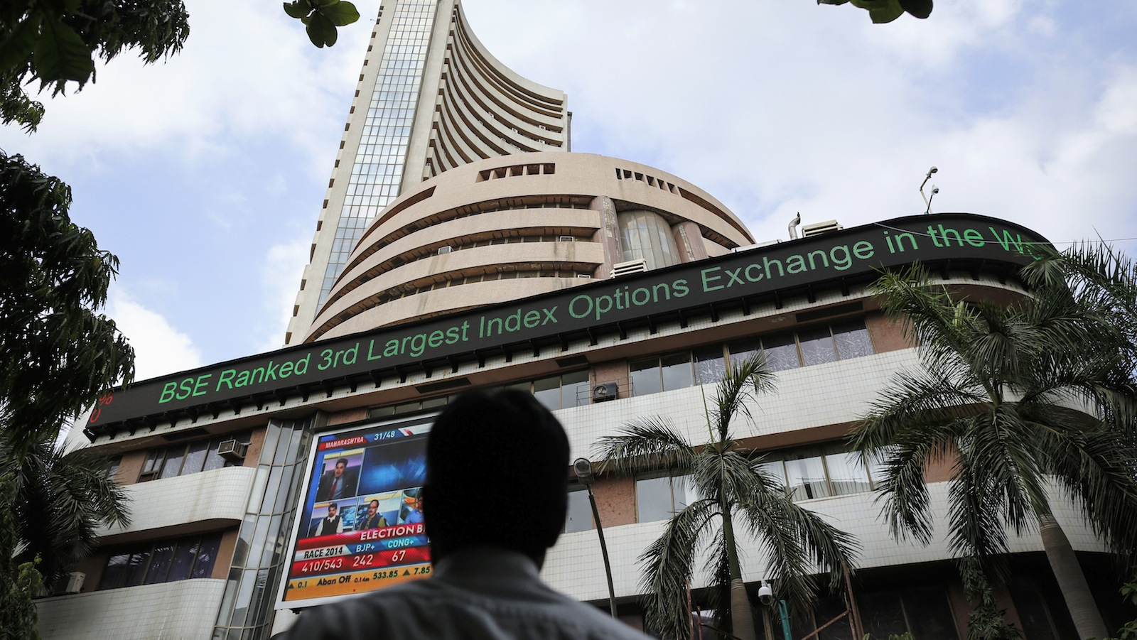 A man looks at a screen across the road displaying the election results on the facade of the Bombay Stock Exchange (BSE) building in Mumbai May 16, 2014. Indian shares rallied to record highs, while the rupee strengthened to near a 10-month high against the dollar, as early vote counts in the country's general elections showed the opposition Bharatiya Janata Party and its allies leading.