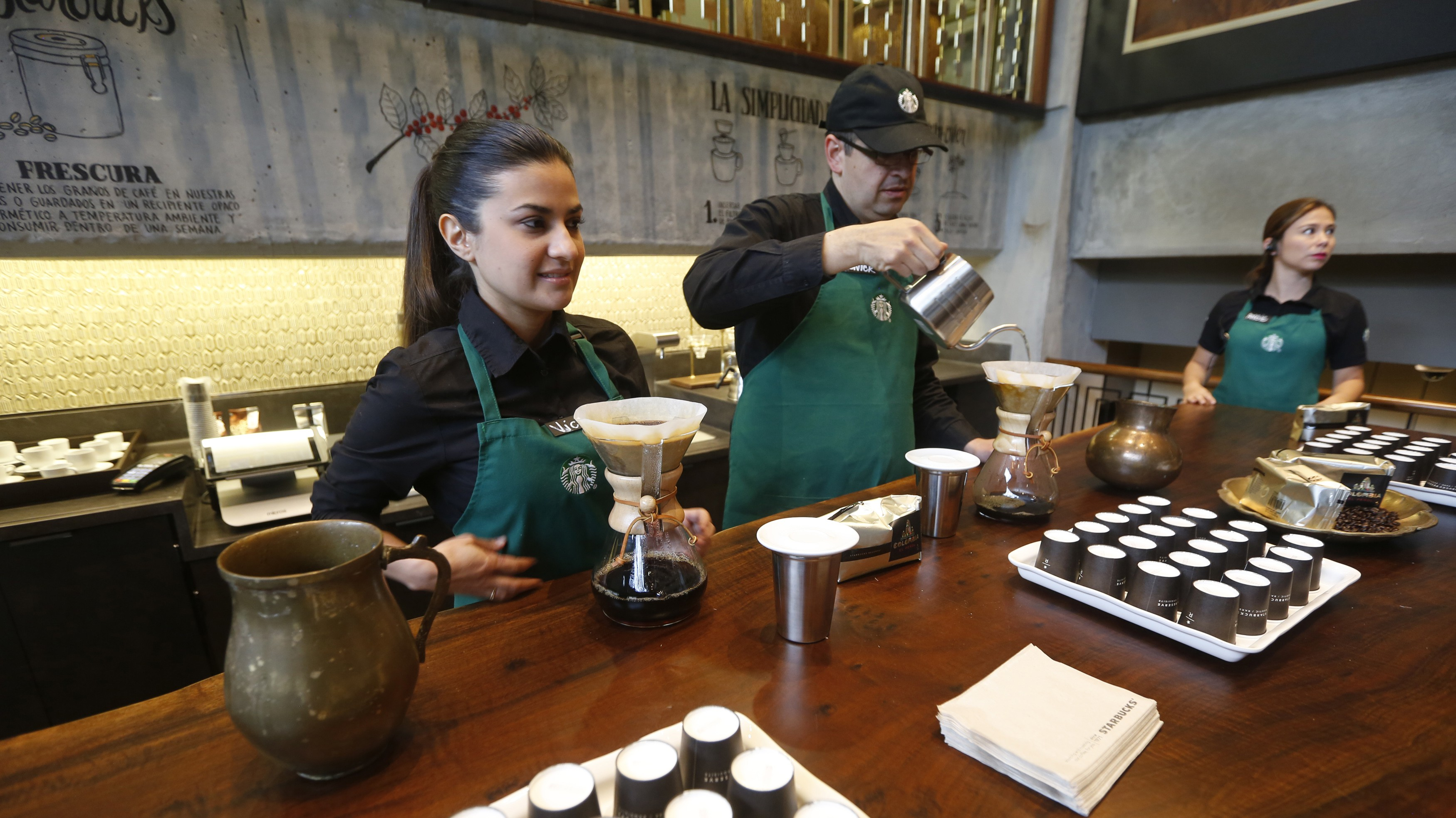 Workers prepare coffee during the inauguration of Starbuck's first Colombian store at 93 park in Bogota July 16, 2014. Starbucks Corp opened its first shop in Colombia on Wednesday, 43 years after the world's biggest coffee chain first started buying beans from the country famous for its premium arabica coffee named after fictional coffee farmer Juan Valdez.