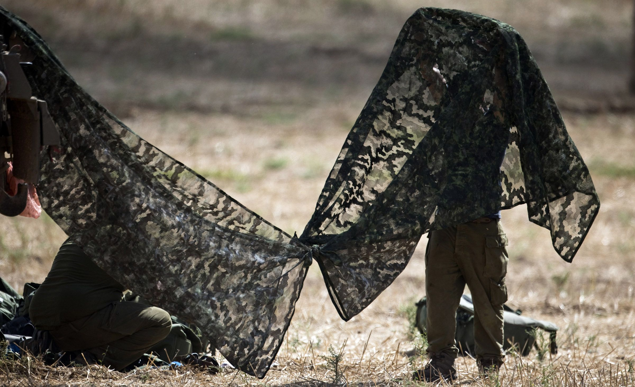 An Israeli army reservist fixes a camouflage net in a staging area outside the Gaza Strip July 18, 2014. Israel stepped up its ground offensive in Gaza early on Friday pounding targets with artillery fire and using tanks and infantry to battle Hamas fighters. Orange flashes illuminated the eastern Gaza Strip as Israeli gunboats off the Mediterranean coast fired shells and tracer bullets, and helicopters fired across the border. Hamas fired rockets back into Israel towards the southern towns of Ashdod and Ashkelon. Palestinian health officials said 23 Palestinians had been killed since Israel launched its ground offensive against the densely-populated strip of 1.8 million Palestinians on Thursday. Israel said one of its soldiers had been killed in fighting.