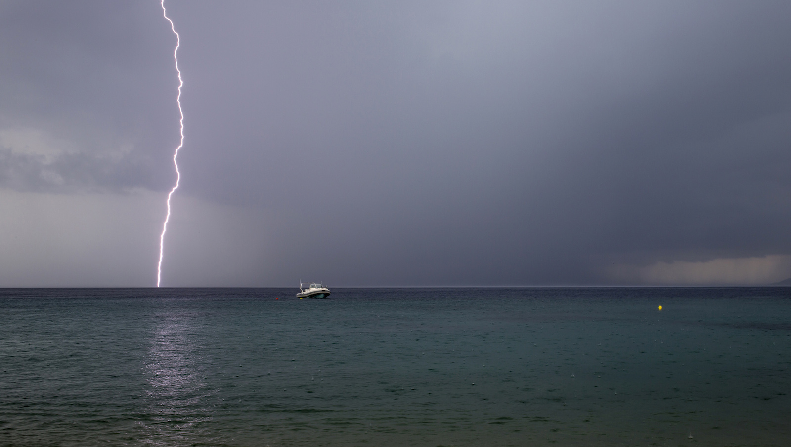 Lightning strikes as a small boat is seen at the beach in the northern Greek village of Toroni August 1, 2014. (GREECE - Tags: SOCIETY ENVIRONMENT) - RTR40XLC