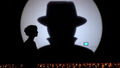 Speaker liaison Genevieve Netter is silhouetted against a Black Hat logo during the Black Hat USA 2014 hacker conference at the Mandalay Bay Convention Center in Las Vegas, Nevada August 6, 2014.