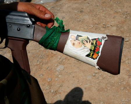 A fighter from the Shi'ite Badr Brigade militia shows a religious sticker on the stock of his AK-47 machine gun outside the town of Sulaiman Pek