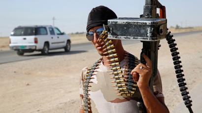 A fighter from the Shi'ite Badr Brigade militia holds his gun at a mobile checkpoint in Suleiman Beg