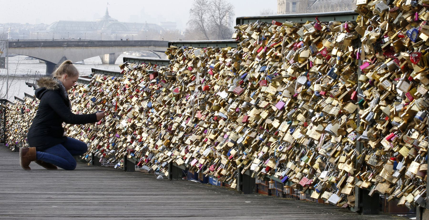 A tourist attaches a love lock on a fence on the access ramp to the Pont des Arts over the River Seine in Paris which is covered with thousands of padlocks January 20, 2015.    REUTERS/Charles Platiau (FRANCE - Tags: TRAVEL SOCIETY) - RTR4M6BW