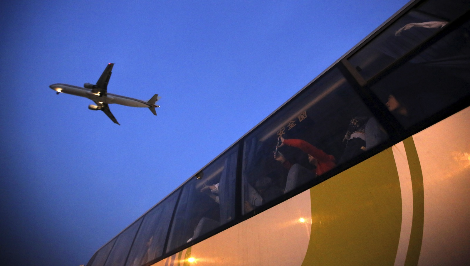 People on a bus look at an airplane as it lands at Hongqiao International Airport in Shanghai April 10, 2015.