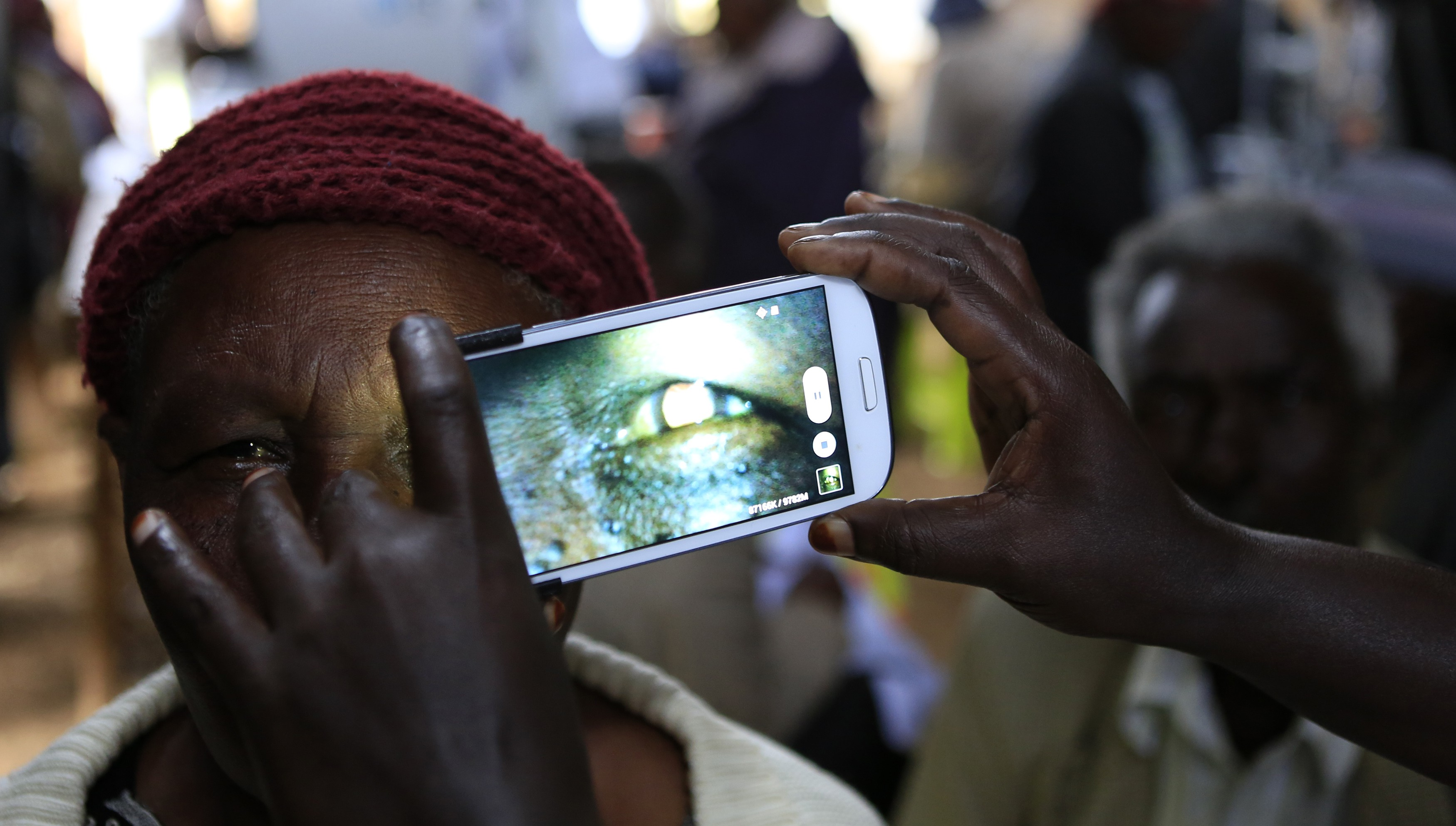 A woman undergoes an eye examination using a smartphone in Kenya. REUTERS/Noor Khamis
