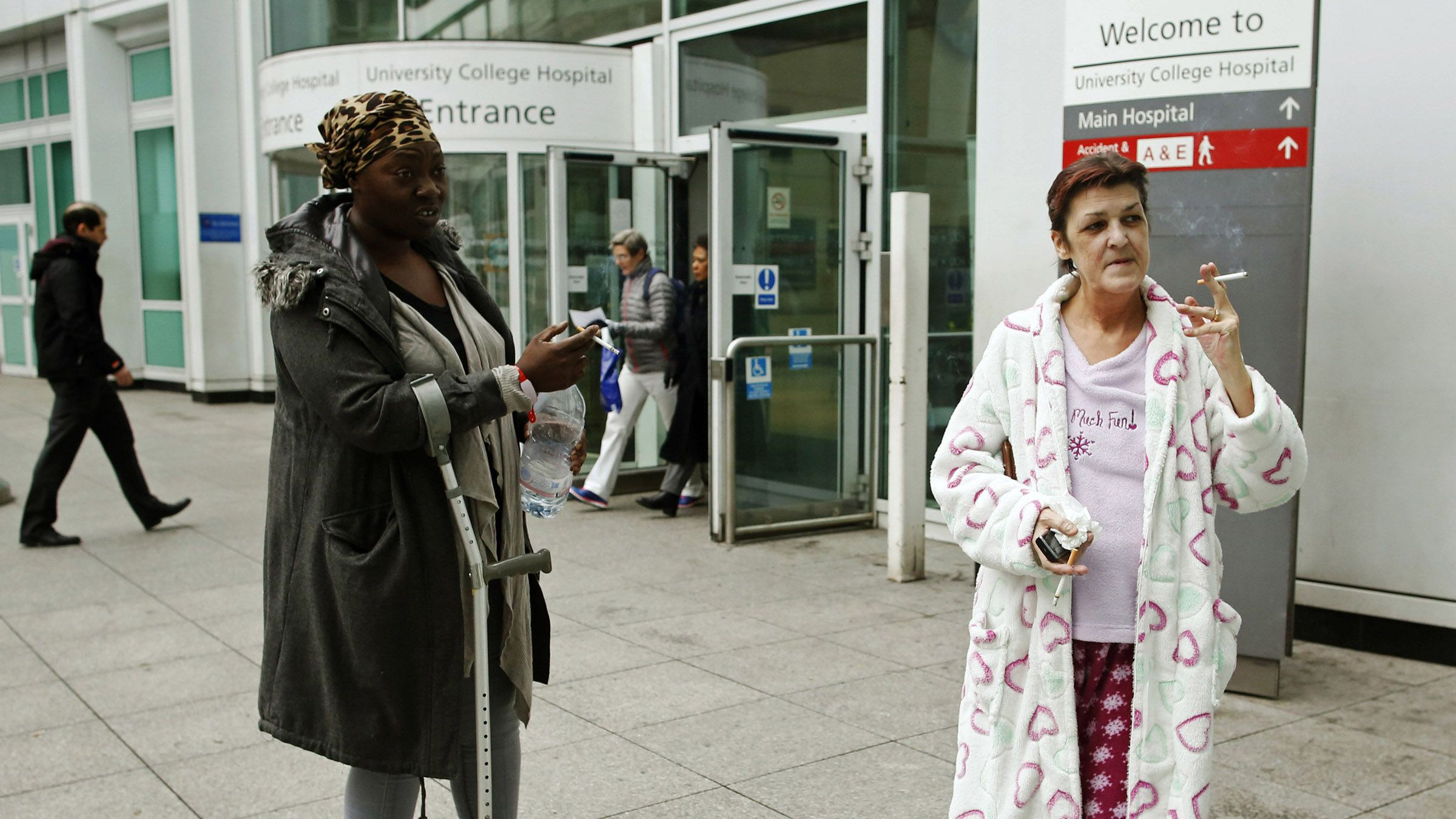 Patient Susan Paul (L) who has smoked for 20 years, stands with throat cancer patient Margaret, who has smoked for 40 years and will have her voice box removed, as they smoke outside University College Hospital in central London November 27, 2013. The National Institute for Health and Care Excellence said Britain's National Health Service should ban smoking at all hospital grounds in England.