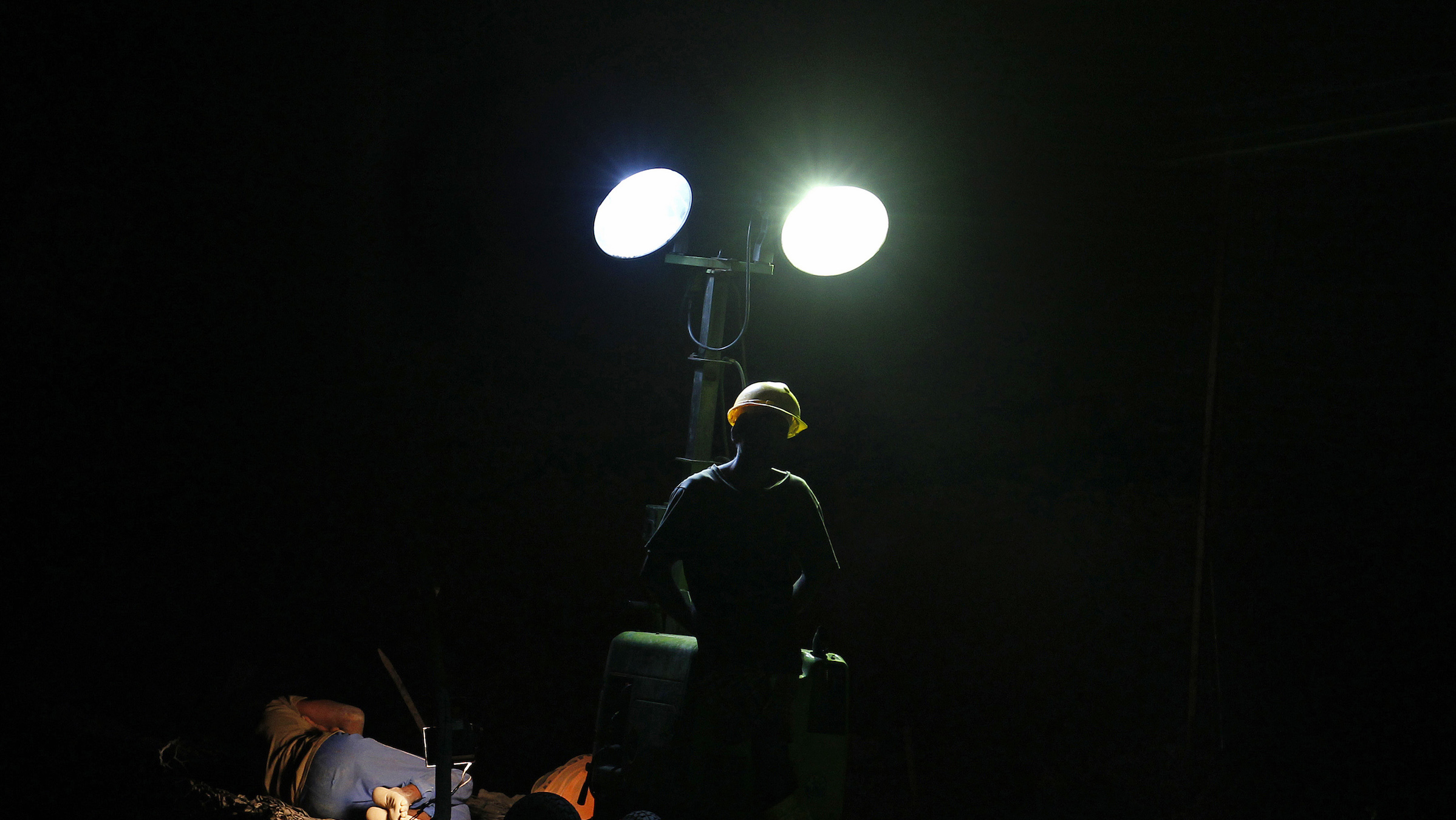 A worker stands next to a light stand as another worker sleeps after an overnight shift at a road construction site in Colombo, early morning January 4, 2014. REUTERS/Dinuka Liyanawatte (SRI LANKA - Tags: BUSINESS CONSTRUCTION SOCIETY EMPLOYMENT) - RTX171BV