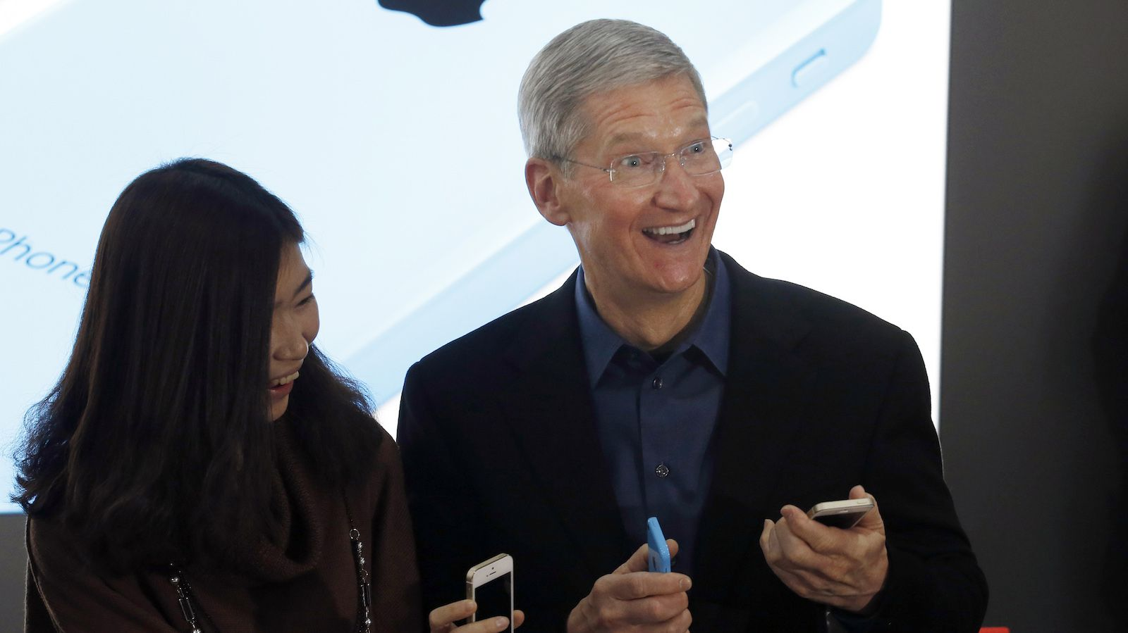 Apple Inc. CEO Tim Cook poses with a customer at an event celebrating the launch of Apple's iPhone on China Mobile's network in Beijing