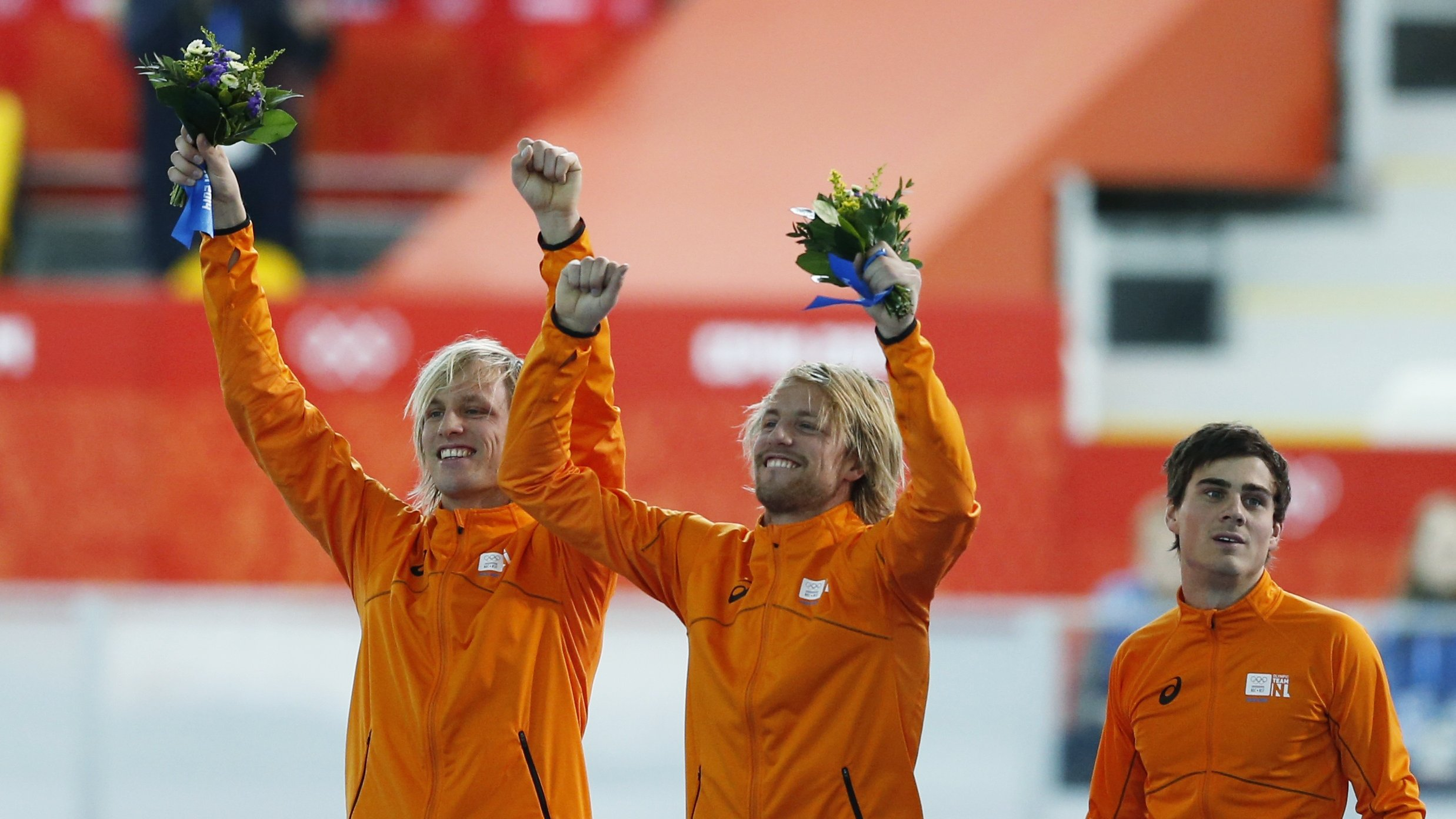 Winner Michel Mulder of the Netherlands (C), his twin brother second-placed Ronald Mulder (L), and their compatriot third-placed Jan Smeekens celebrate during the flower ceremony for the men's 500 metres speed skating race at the Adler Arena during the 2014 Sochi Winter Olympics February 10, 2014. REUTERS/Issei Kato (RUSSIA  - Tags: OLYMPICS SPORT SPEED SKATING)   - RTX18JJ0