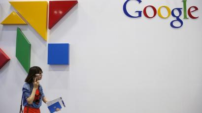 A woman walks past a logo of Google .