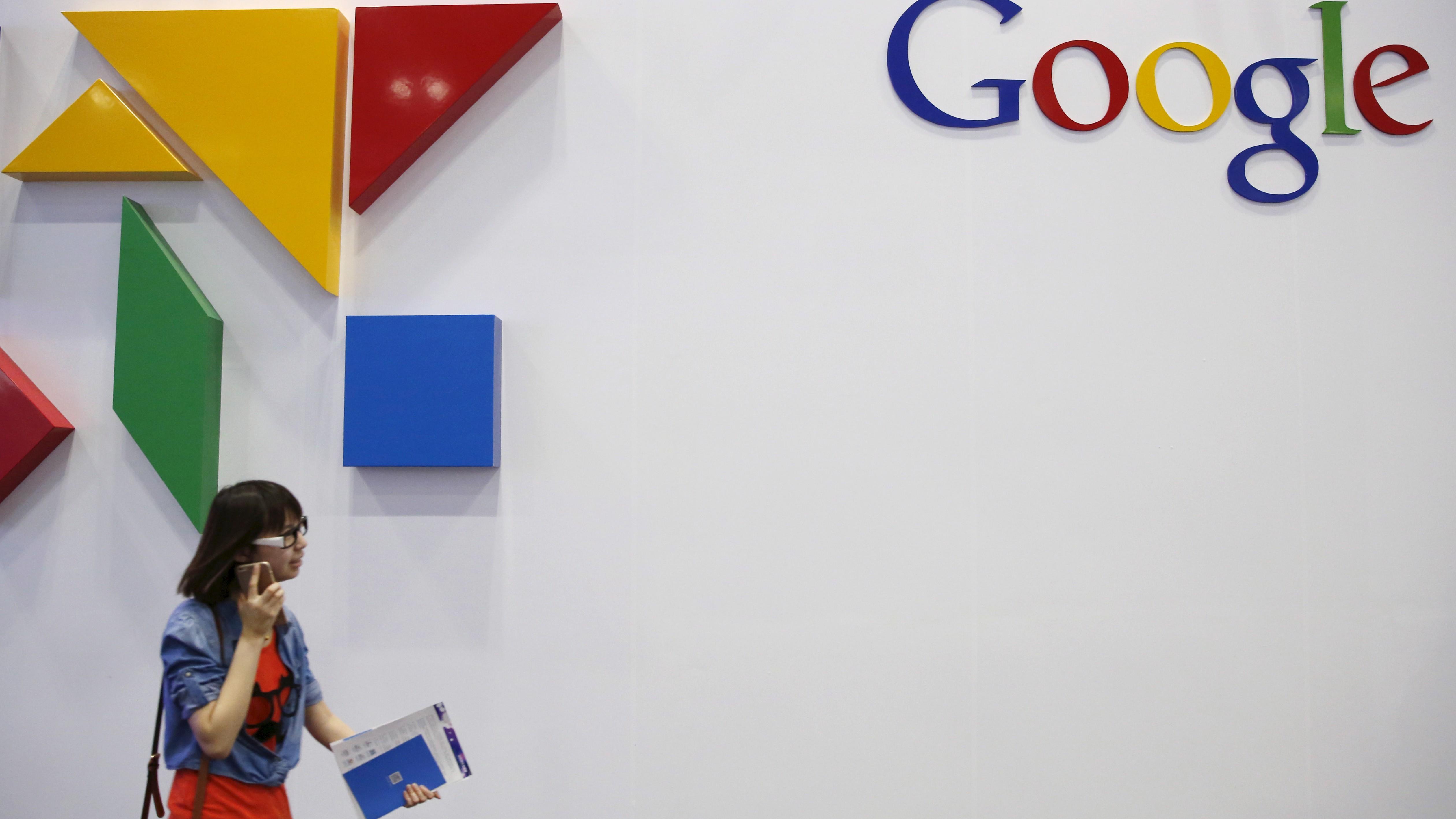 A woman walks past a logo of Google .