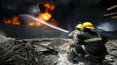 Firefighters attempt to control a fire at a factory Valenzuela City, north of Manila, on May 13.
