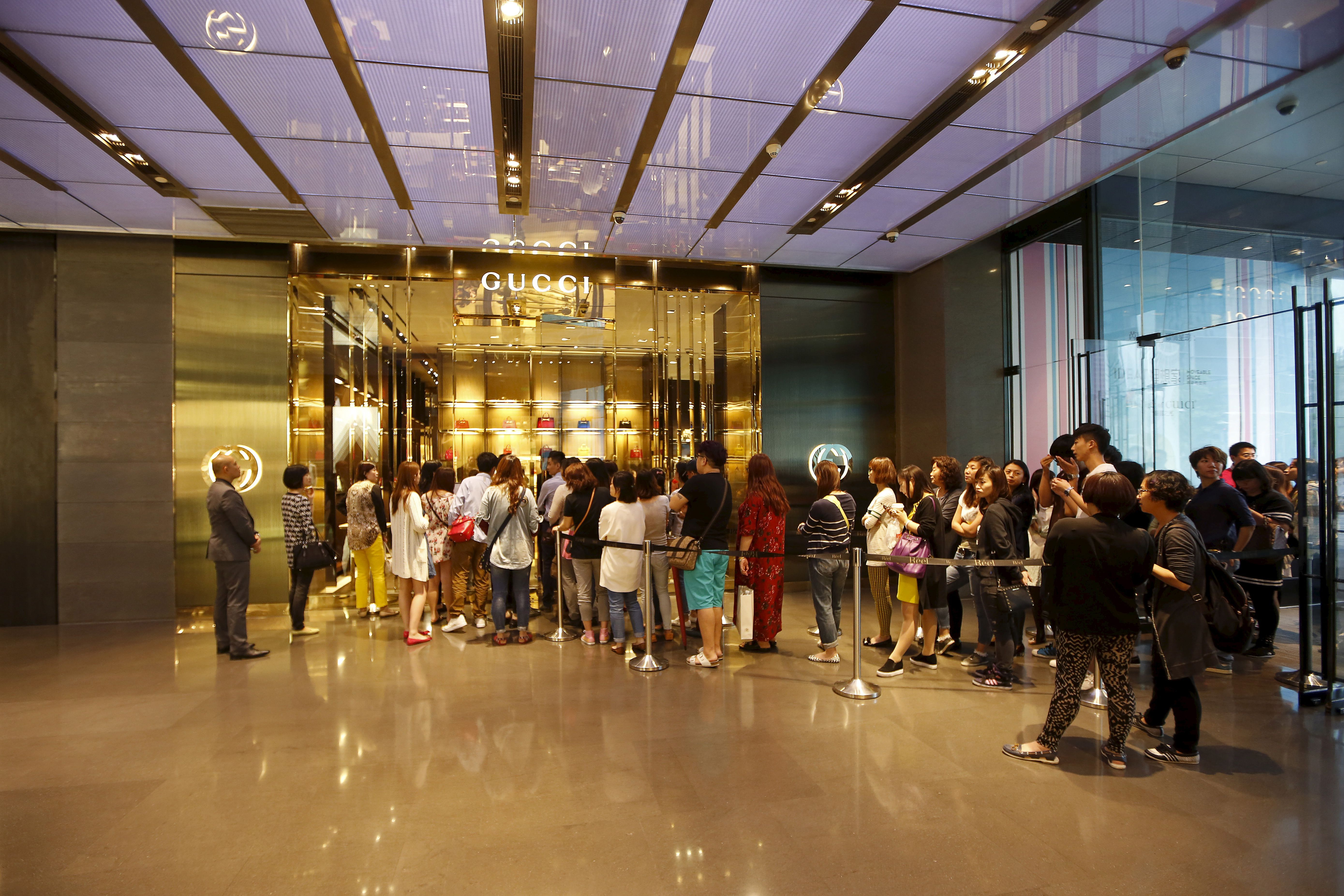 Customers line up as they wait to go inside a Gucci shop at a shopping mall in Shanghai, May 27, 2015.