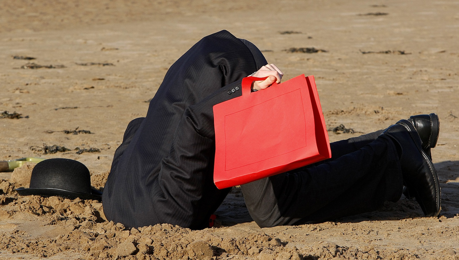 A protestors from the 'Put People First' action group puts his head in the sand as he poses for the photographers on a beach to protest during the G20 Finance Ministers meeting in St Andrews, Scotland November 7,2009. A tax on financial transactions to fund future bank bailouts should be considered with urgency, British Prime Minister Gordon Brown said on Saturday, a significant departure from London's line to date.   (BRITAIN POLITICS BUSINESS) - RTXQGLR