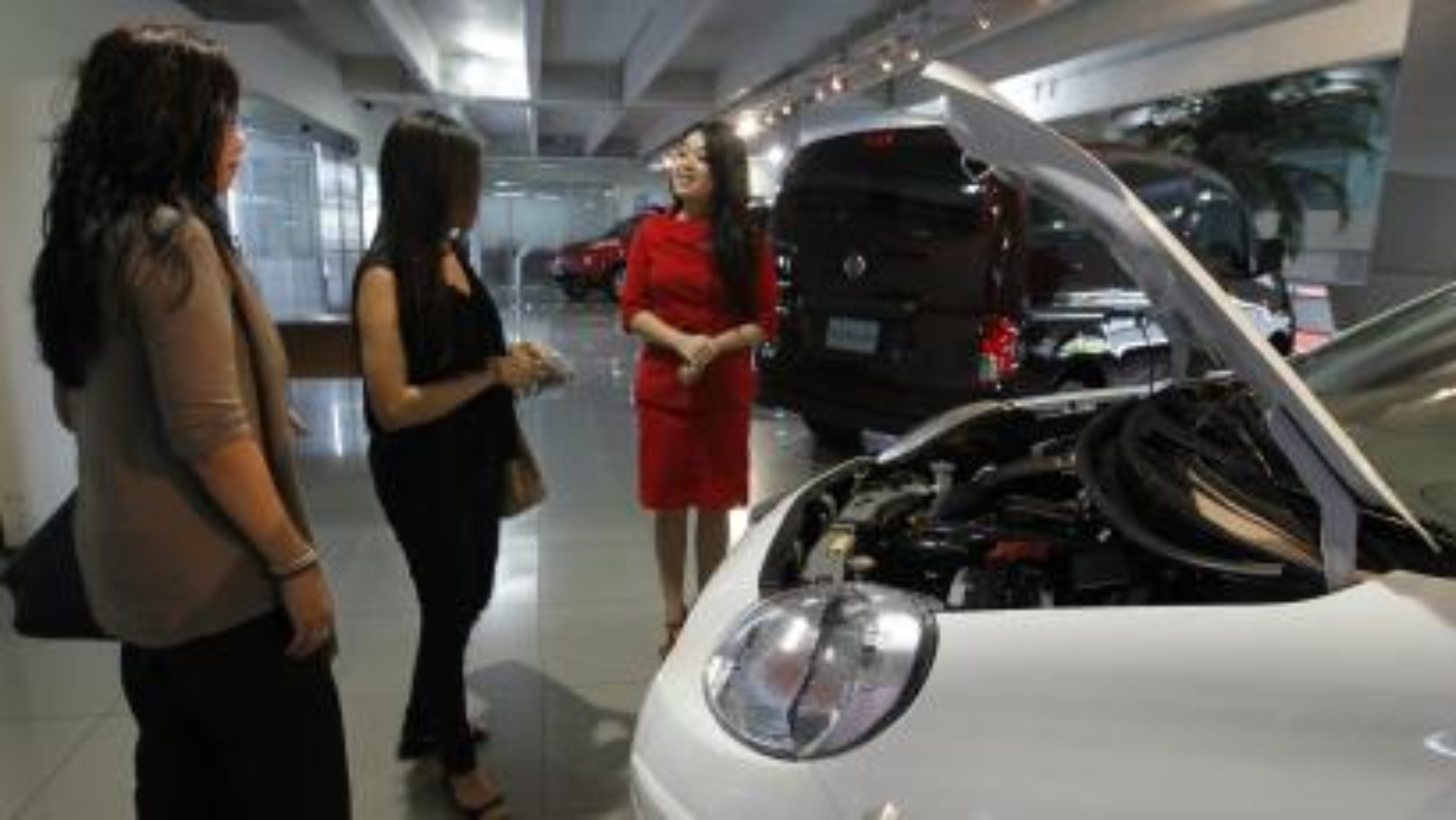 A saleswoman talks to customers at a Nissan dealership in Jakarta, Indonesia.
