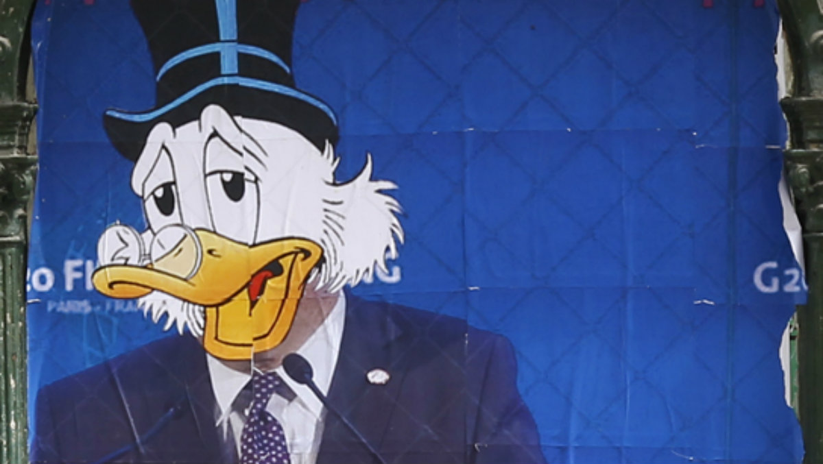 A street art poster shows former IMF head Dominique Strauss-Kahn portrayed as cartoon character Scrooge McDuck.