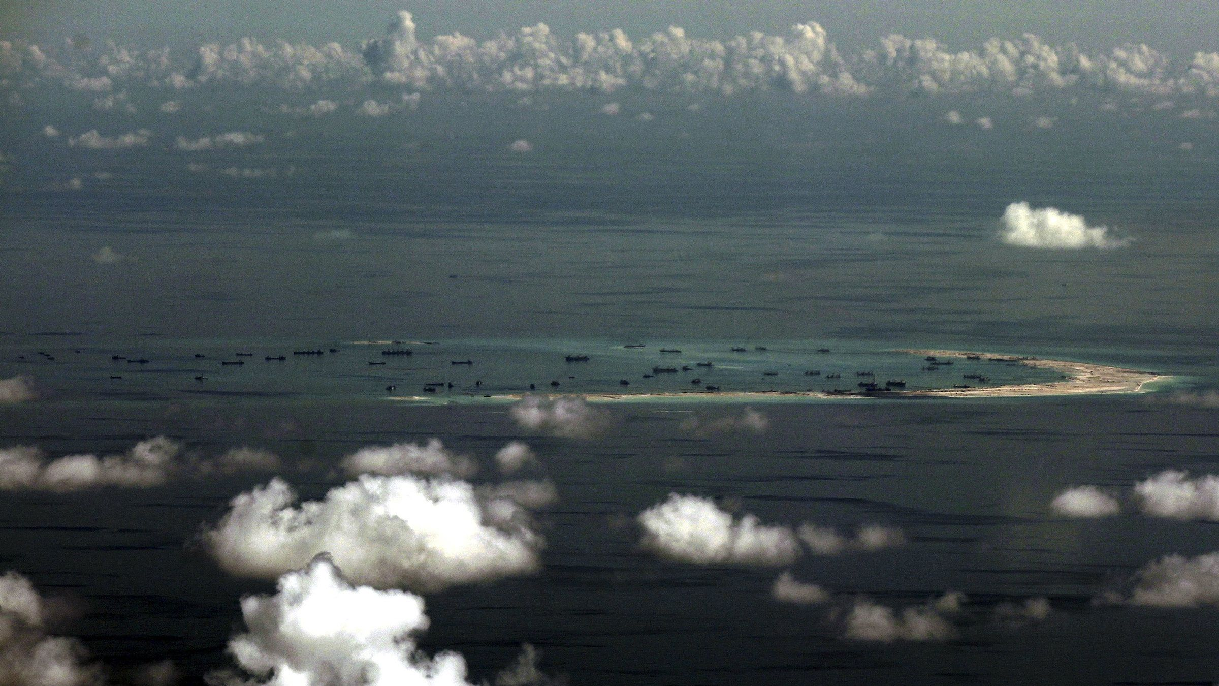 An aerial photo taken though a glass window of a Philippine military plane shows land reclamation by China around the Spratly Islands in the South China Sea.