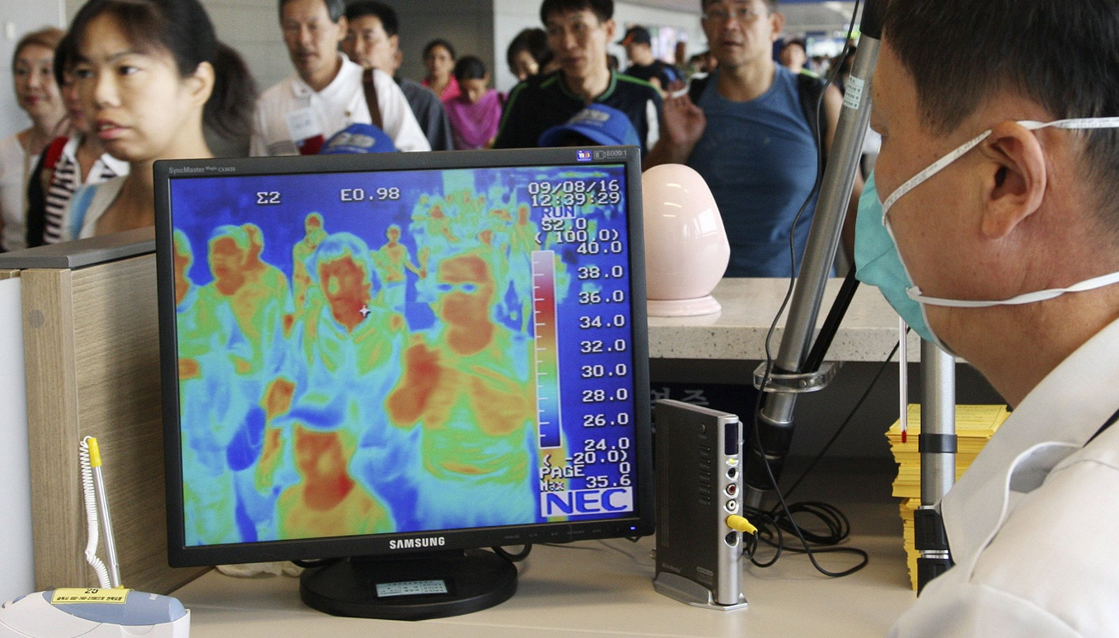 A South Korean quarantine officer checks a thermal camera monitoring the body temperature of passengers arriving from overseas against the possible infection of swine flu at Incheon International Airport in Incheon, west of Seoul, South Korea, Sunday, Aug. 16, 2009. South Korea says a woman infected with swine flu has died, becoming the country's second fatality linked to the virus.(AP Photo/Yonhap, Ahn Jung-hwan