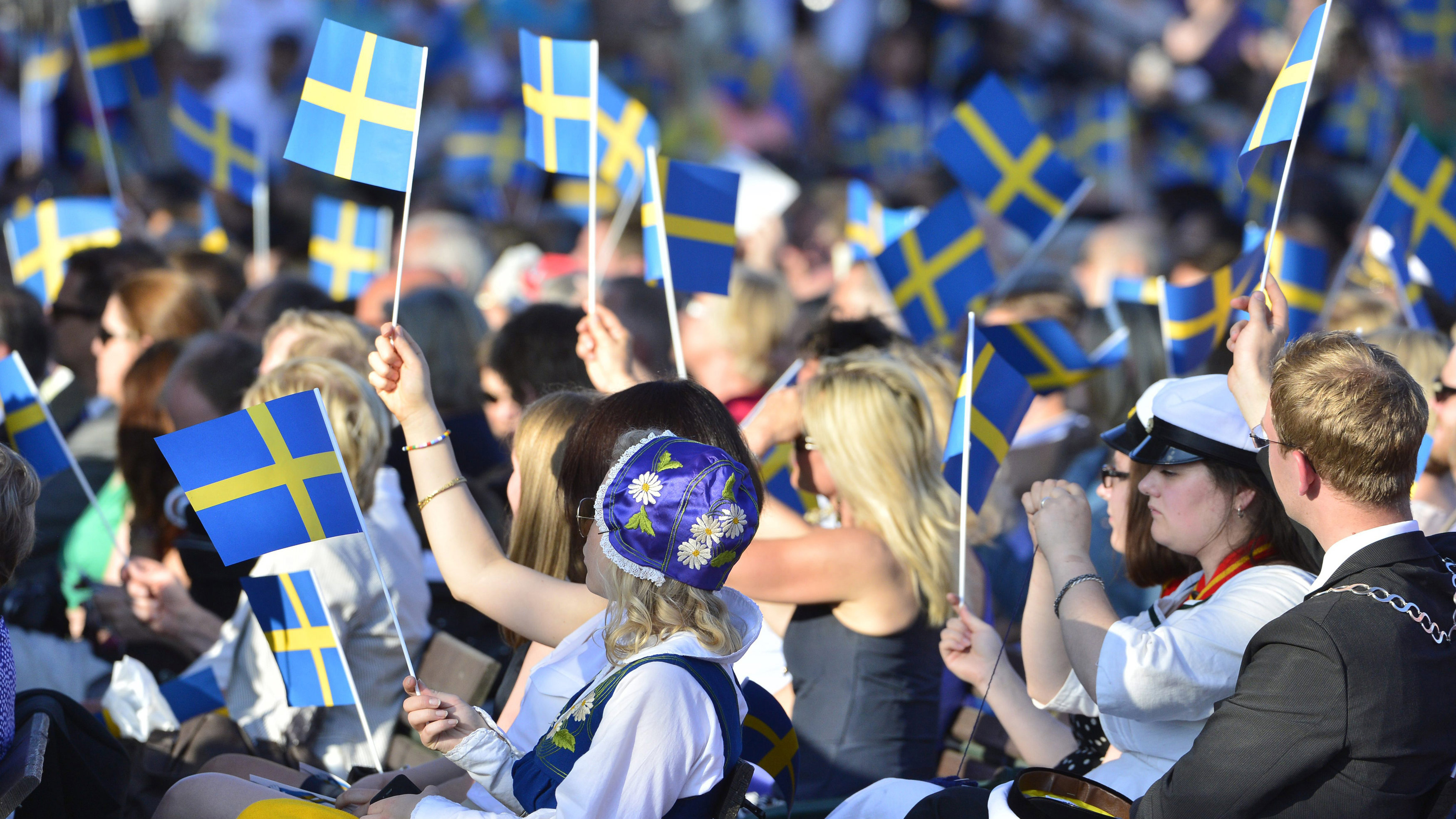 People in the audience wave Swedish flags during the traditional National Day celebrations with the royal family at Skansen in Stockholm June 6, 2013.