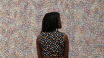 """A visitor poses with artist James Hugonin's """"Binary Rhythm (I)"""" at the press view of the Summer Exhibition 2011 at the Royal Academy of Arts in London, June 2, 2011."""