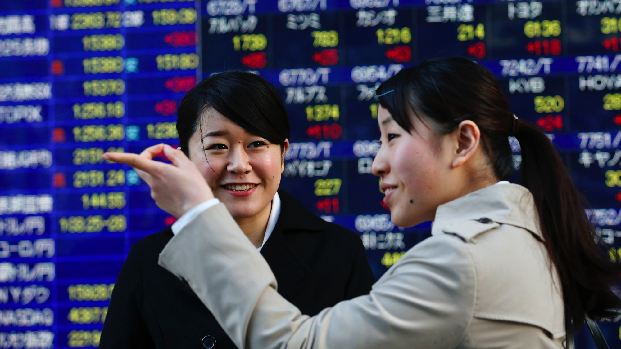 Women chat in front of a securities firm in Tokyo, Wednesday, Jan. 29, 2014. Global stock markets rose Wednesday as jitters about emerging economies were soothed by the Turkish central bank's aggressive interest rate hike to stabilize its currency and China's infusion of funds into its banking system. Japan's Nikkei 225 jumped 2.7 percent, closing at 15,383.91. (AP Photo/Shizuo Kambayashi)