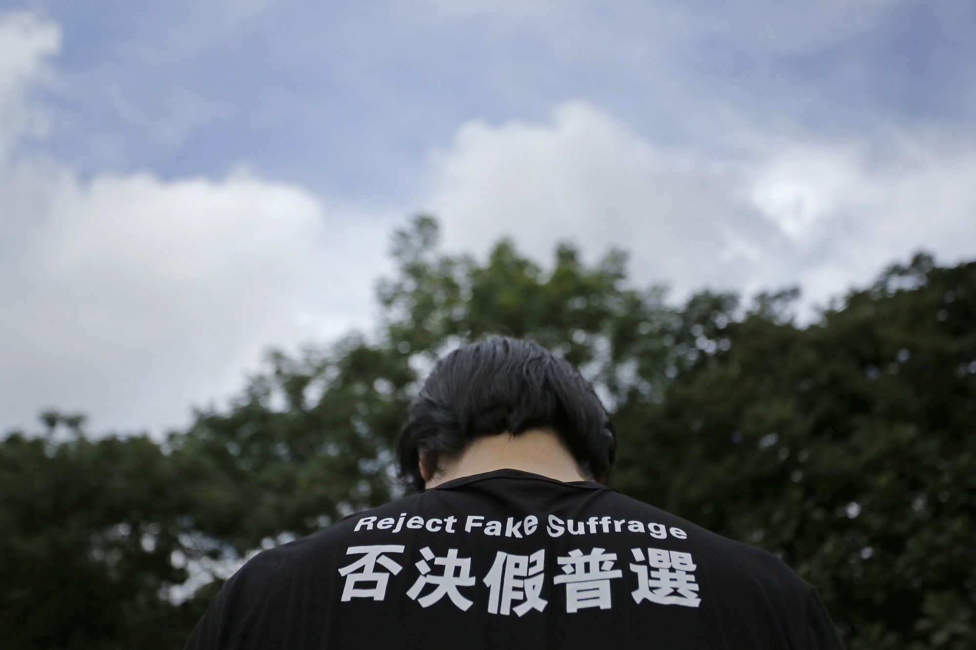 A protester wears a T-shirt with slogan during a rally as thousands of people march in a down town street to support for a veto of the government's electoral reform package in Hong Kong, Sunday, June 14, 2015. the rally is ahead of a crucial vote by lawmakers on controversial Beijing-backed election reforms that drew huge crowds of protesters into the streets last year.