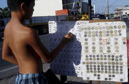 A teenager places bets on a numbers game along a road in San Fernando city, north of Manila.