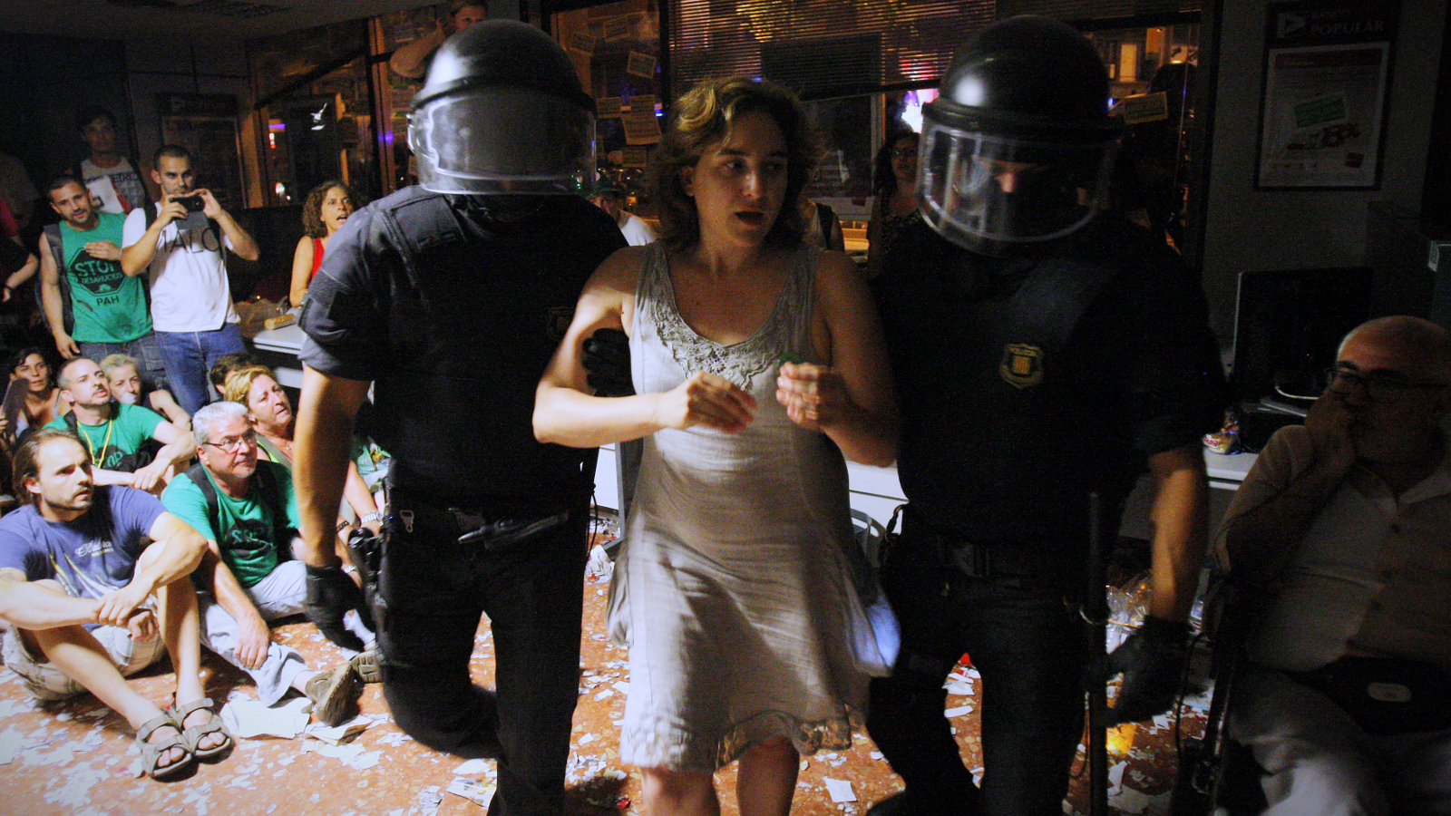 Ada Colau, new mayor of Barcelona, is carried out by riot police officers after occupying a bank in 2013