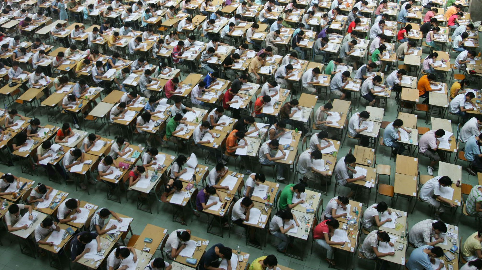 Students sit an English examination in the hall of a building in the Dongguan Technology Institute, in China's southern Guangdong Province, Monday, July 9, 2007. Some 1,200 students of different year levels were made to sit different exams in the hall in an effort to prevent cheating. (AP Photo/EyePress