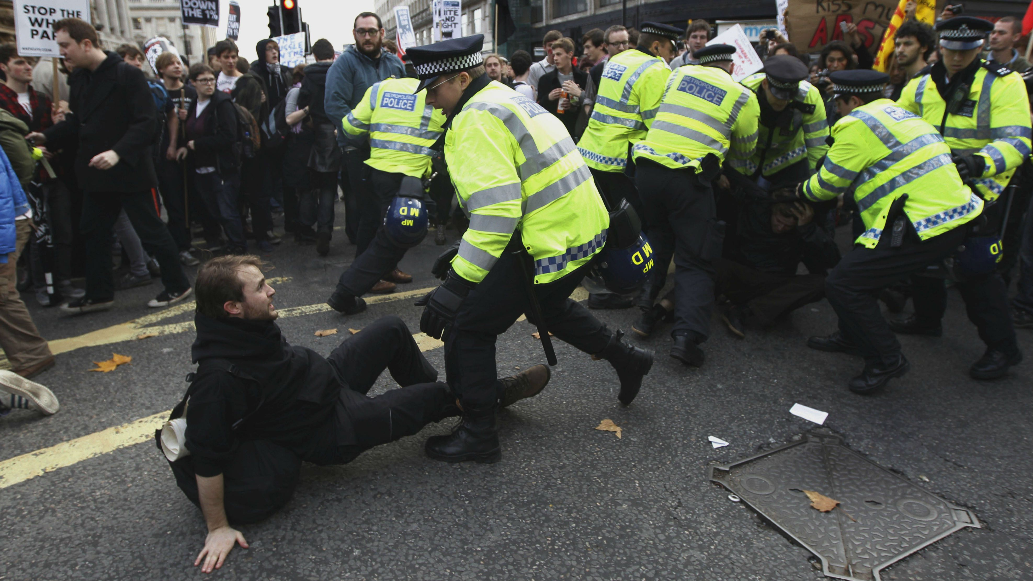 """British police officers scuffle with students during a protest march in central London, Wednesday, Nov. 9, 2011. Students marched through London Wednesday to protest cuts to public spending and a big increase in tuition fees. Police said more than 2,000 people were taking part as the march set off with chants of """"No ifs, no buts, no education cuts."""" (AP Photo/Lefteris Pitarakis)"""