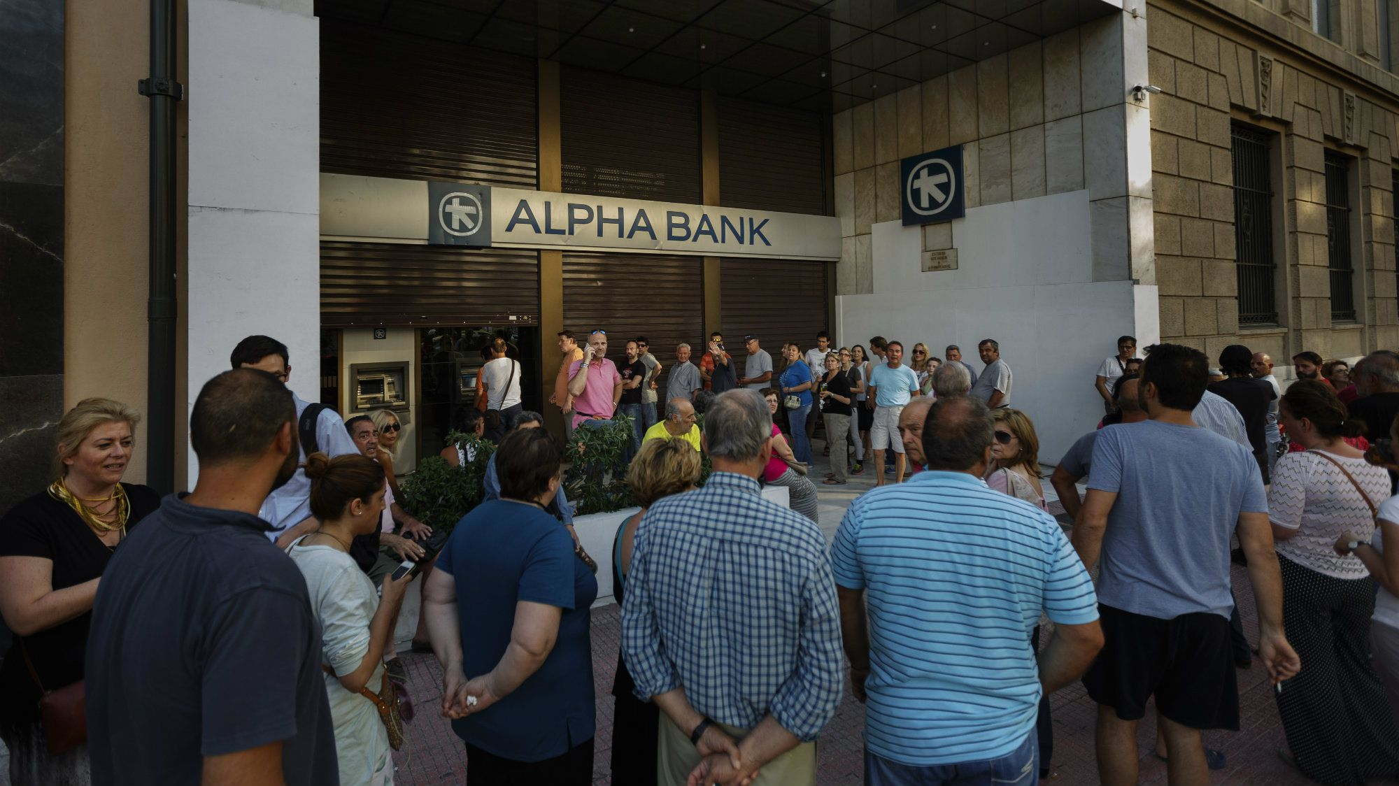 People stand in a queue to use ATM cash machine of a bank in central Athens, Sunday, June 28, 2015. Greece is anxiously awaiting a decision by the European Central Bank on whether to increase the emergency liquidity assistance banks can draw on from the country's central bank.