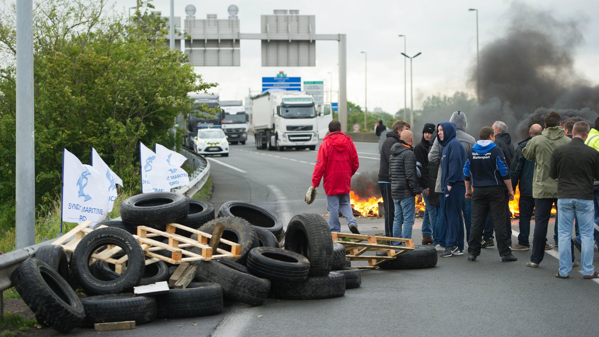 Striking ferry workers burn tyres as they block a ramp leading into the Eurotunnel before being dispersed by riot police in Calais, northern France, Tuesday, June 23, 2015.