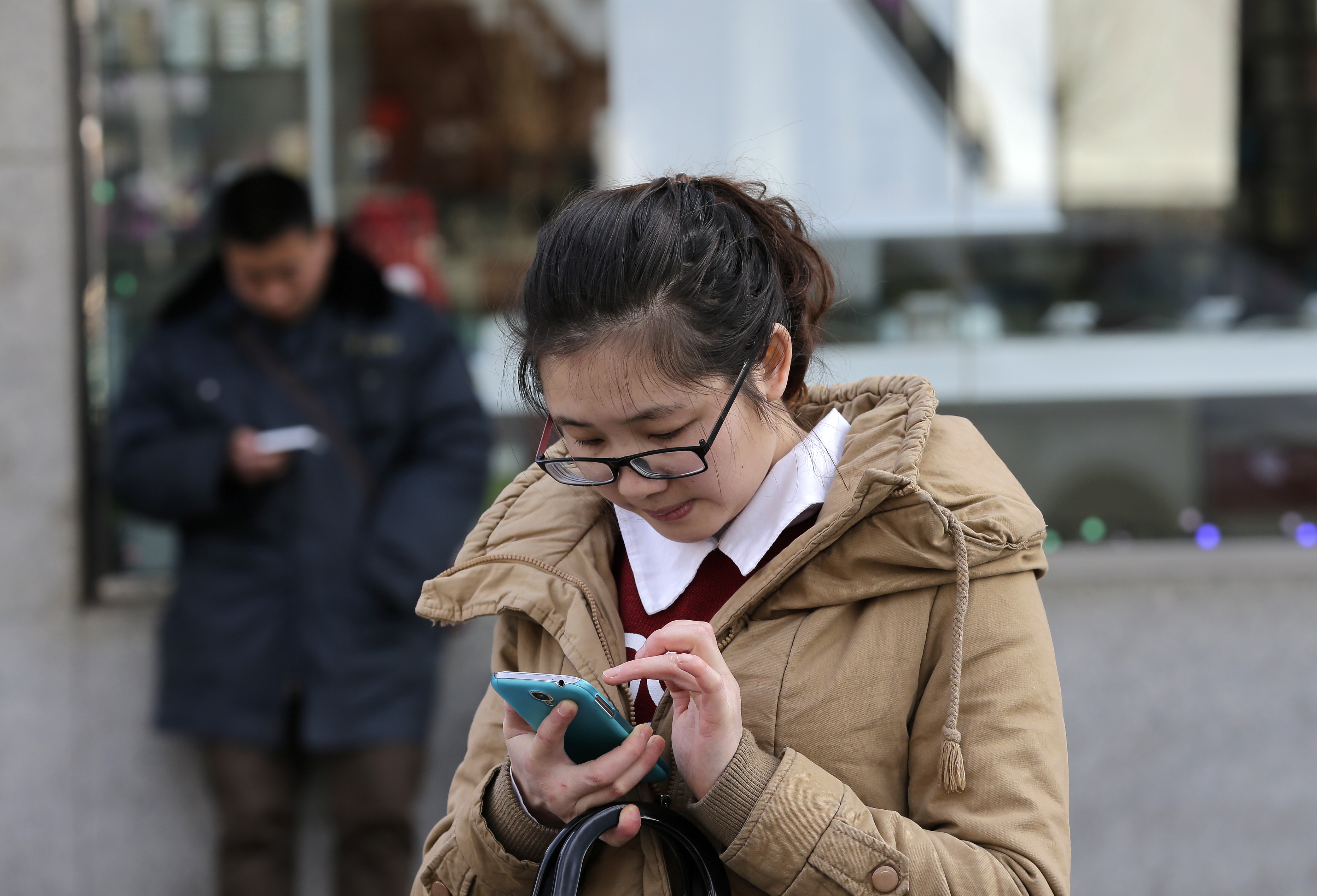 Chinese people check on their smartphones on a street in Beijing Monday, Feb. 16, 2015. On the Internet, in college classrooms and in corporate offices, the Chinese Communist Party has raised the virtual wall separating the world's most populous country from the rest of the globe. Experts say it reflects a distrust of outside influences that party thinks could threaten its control on society.