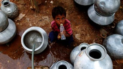 Indian boy drinks water during heat wave