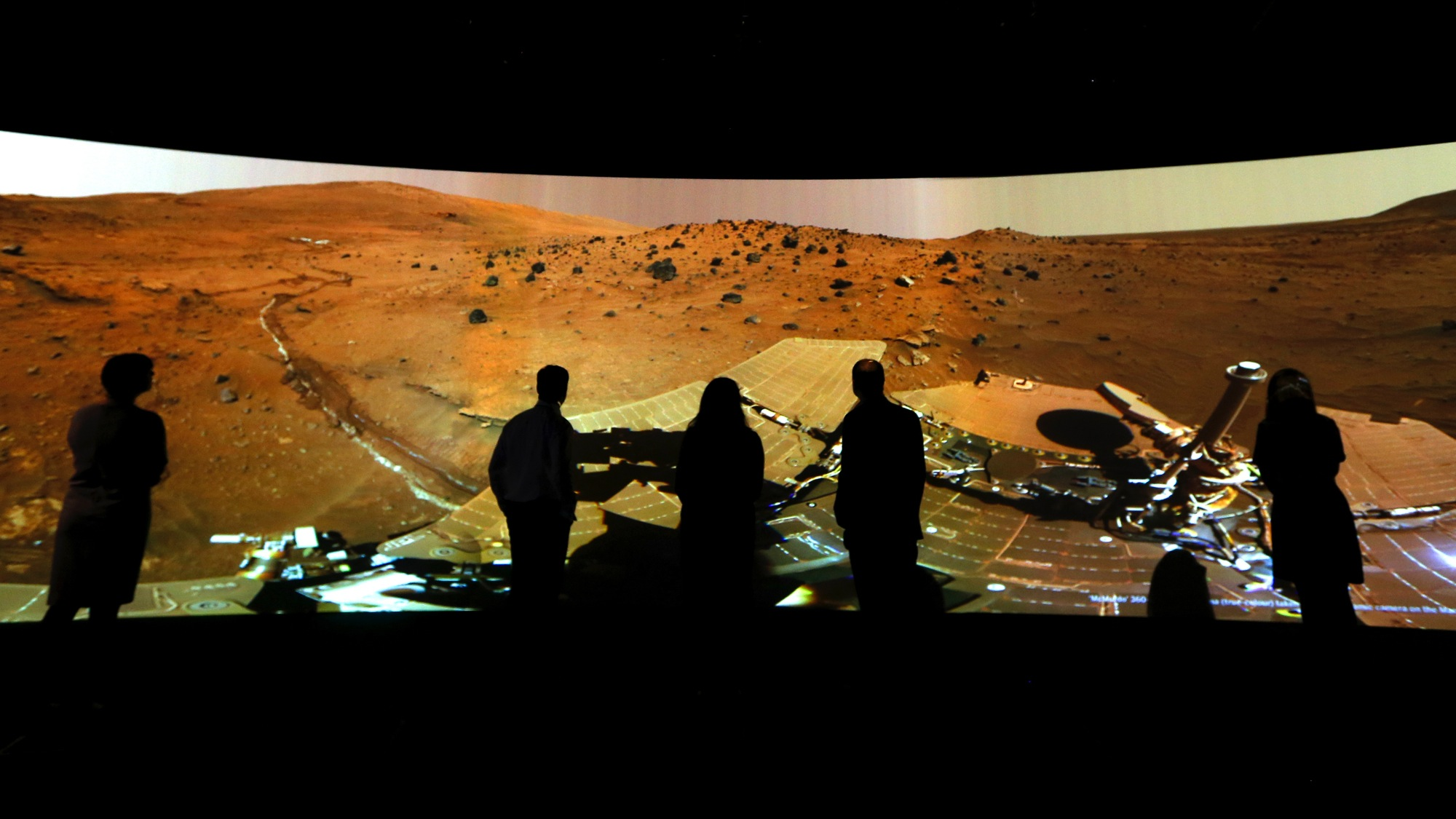 """FILE - In this Wednesday, June 5, 2013 file photo, people look at the """"Mars Window,"""" a projection of images taken by NASA's Mars Curiosity Rover at the Visions of the Universe exhibition at The National Maritime Museum in Greenwich, London. (AP Photo/Kirsty Wigglesworth)"""